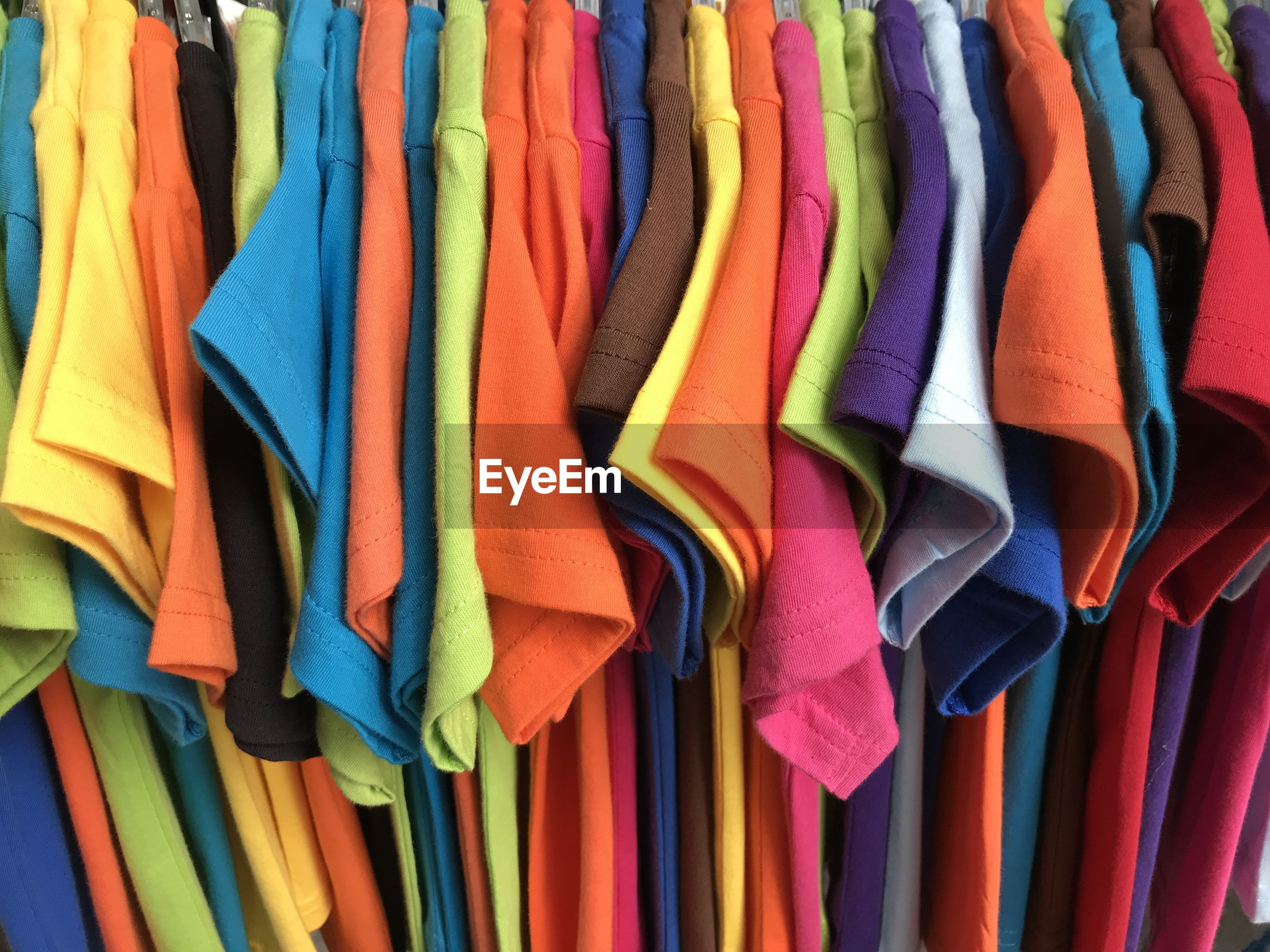Multi colored clothes hanging on display at store