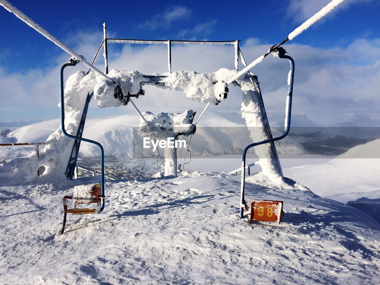 Ski Lifts On Snowcapped Mountain Against Sky
