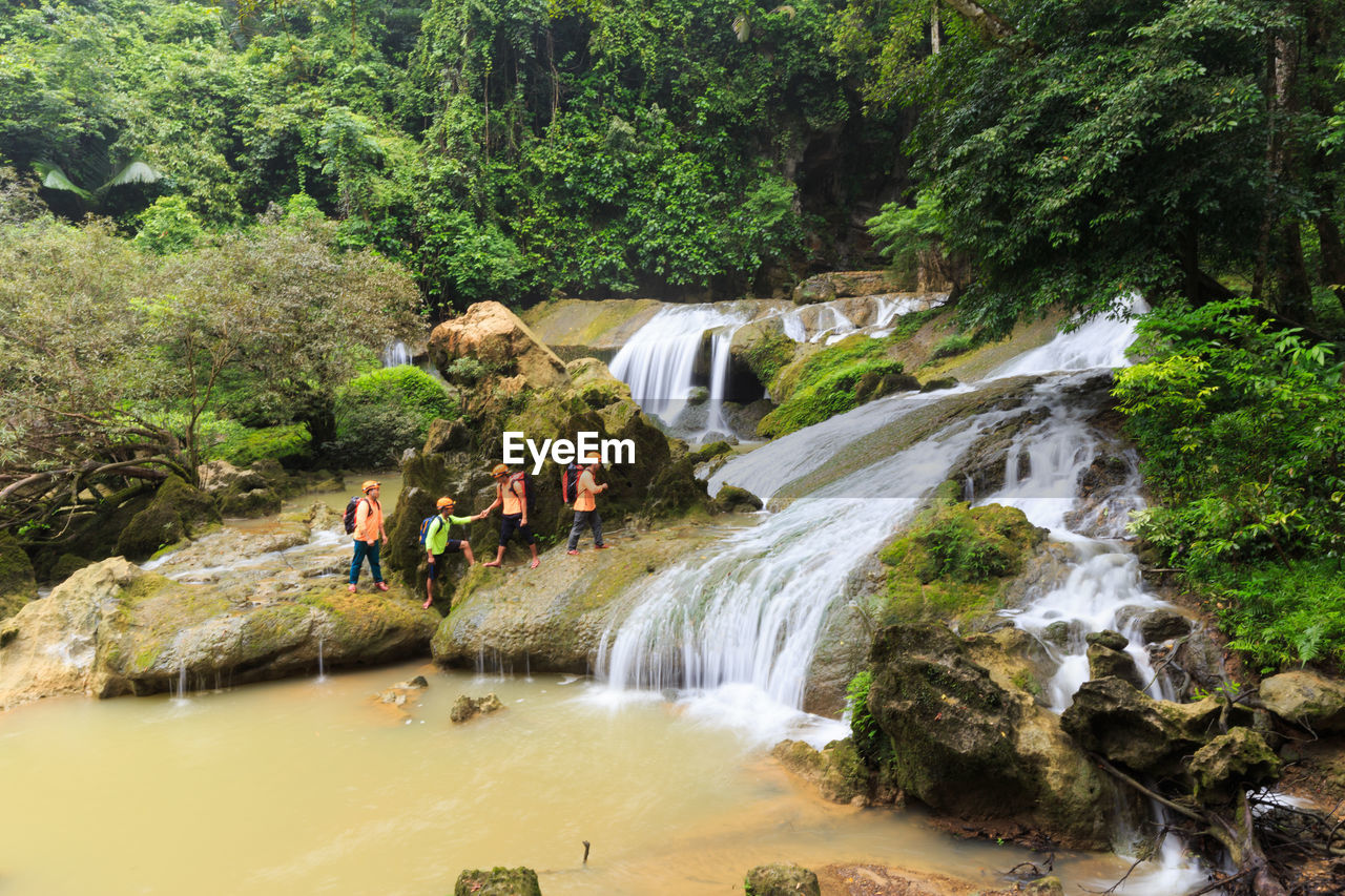 water, tree, plant, waterfall, forest, scenics - nature, beauty in nature, nature, motion, group of people, rock, river, land, long exposure, adult, flowing water, blurred motion, rock - object, men, outdoors, rainforest