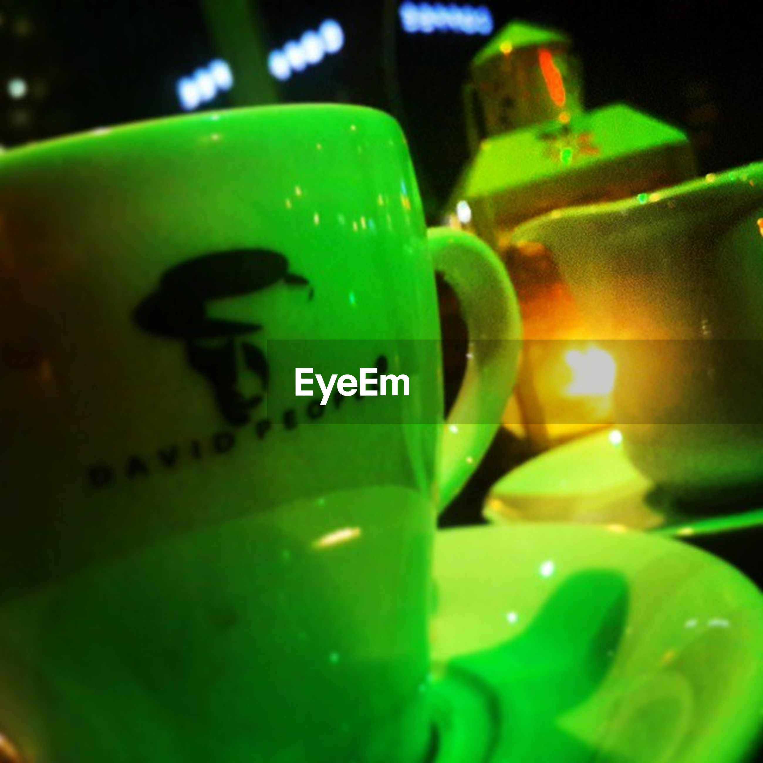 close-up, green color, text, indoors, human representation, western script, communication, still life, art, creativity, art and craft, focus on foreground, animal representation, selective focus, no people, anthropomorphic face, single object, detail, yellow