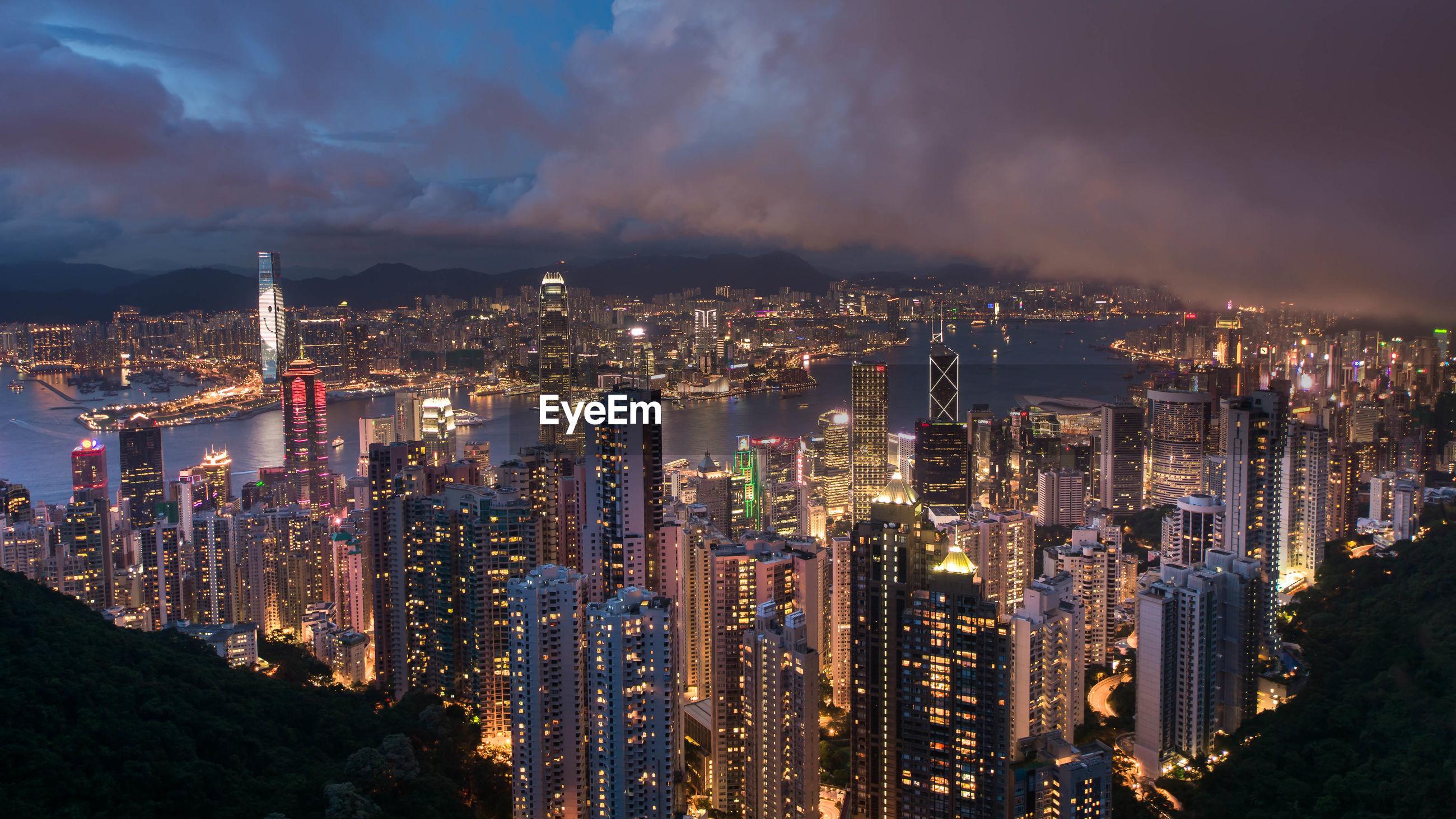 ILLUMINATED MODERN BUILDINGS IN CITY AGAINST SKY