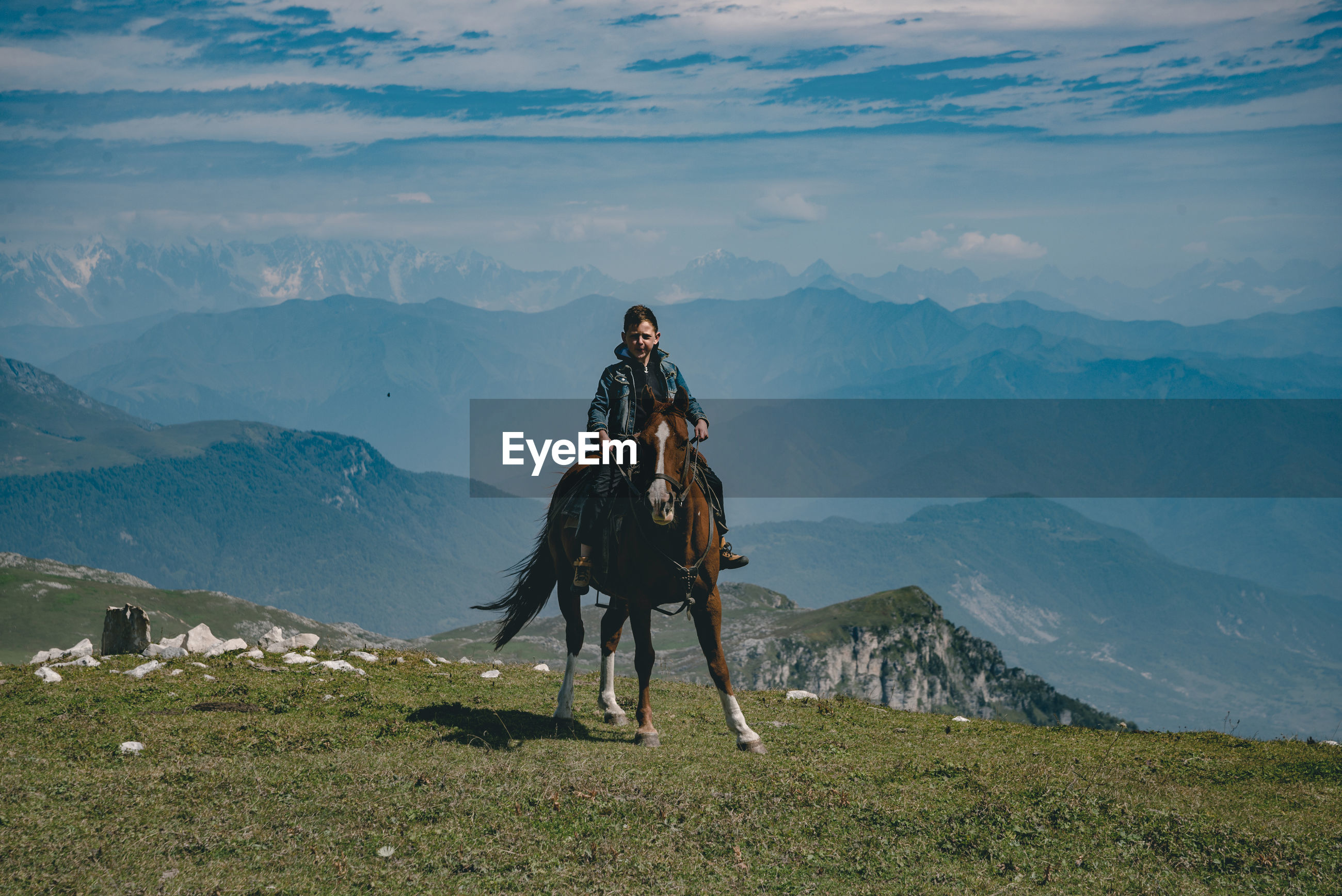 Full length of boy sitting on horse against mountain