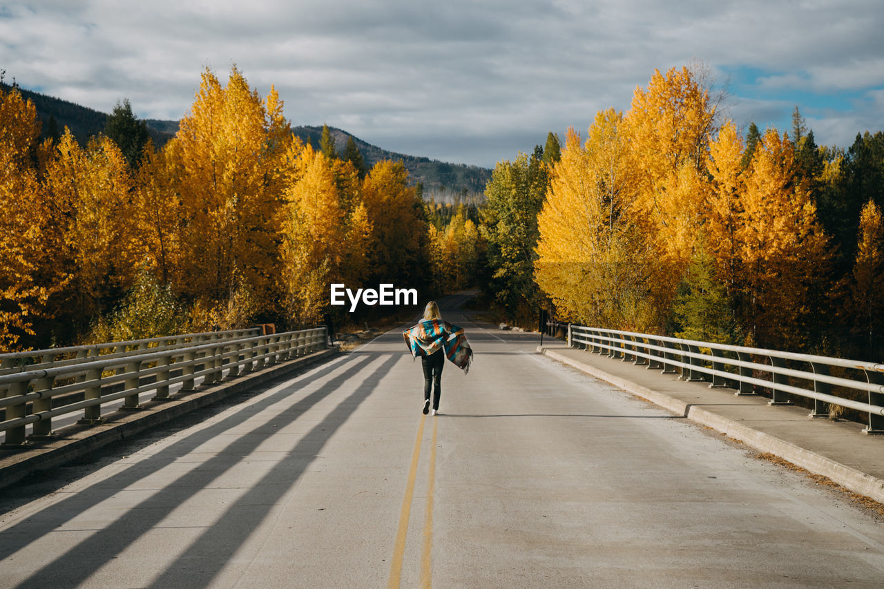 tree, transportation, autumn, real people, road, change, lifestyles, direction, road marking, plant, the way forward, one person, full length, nature, marking, bicycle, riding, ride, sky, symbol, outdoors, diminishing perspective