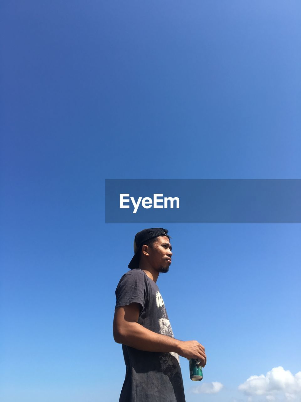 Side view of young man looking away against blue sky