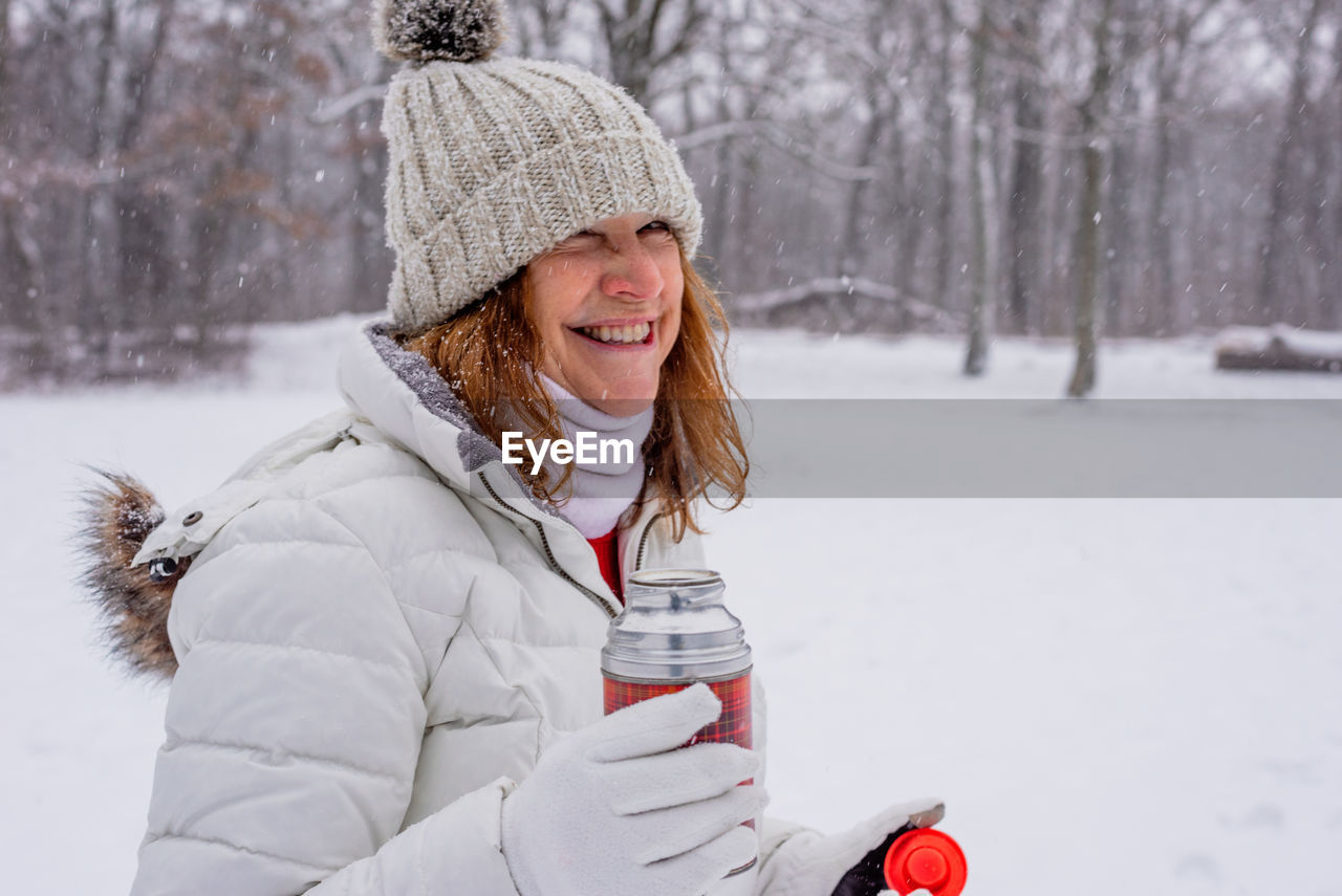 Smiling woman holding bottle while standing in snow outdoors