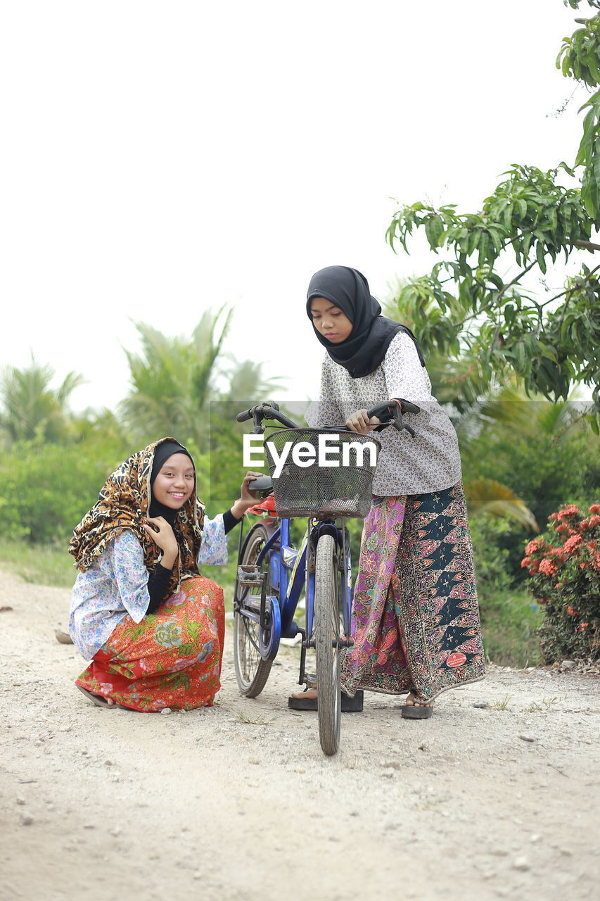 Girls with bicycle on footpath against sky