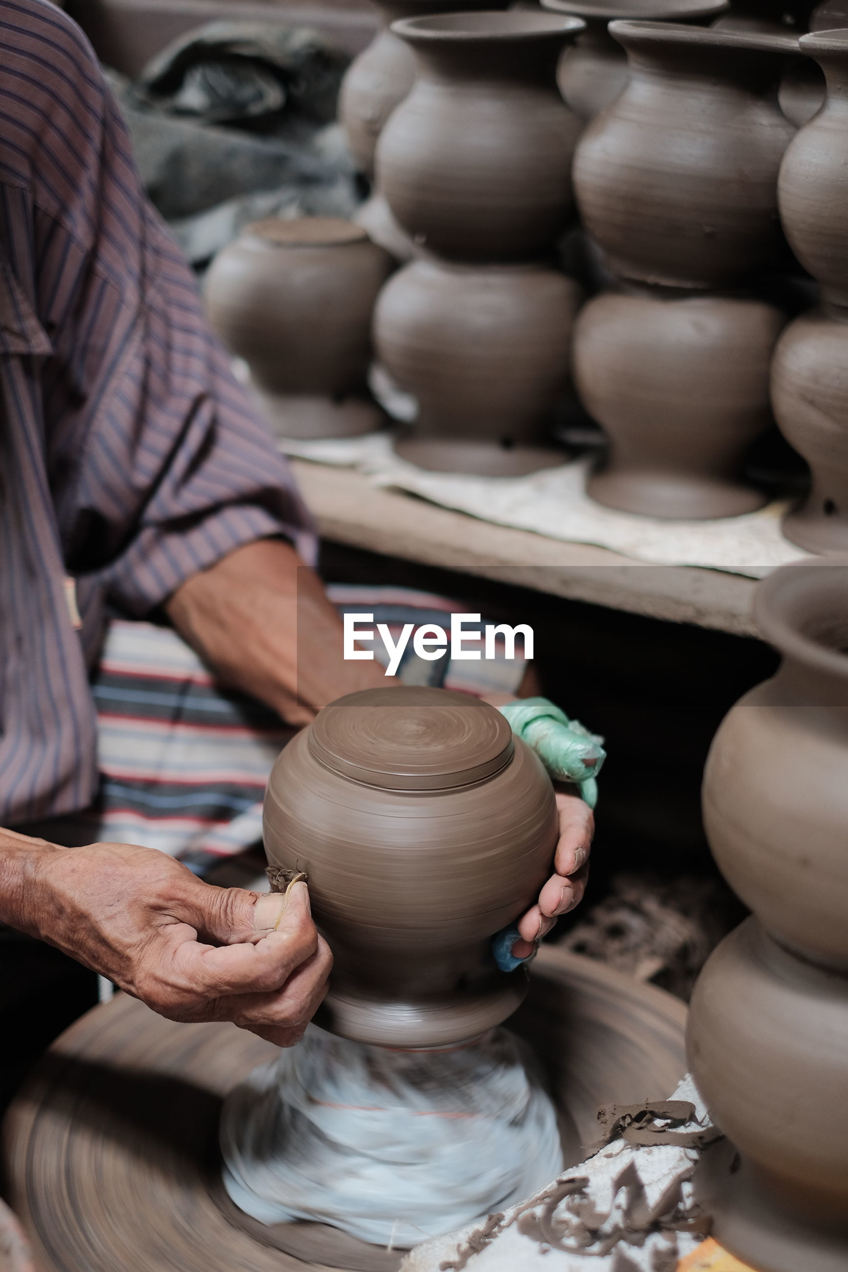 Midsection of potter shaping earthenware on pottery wheel at workshop