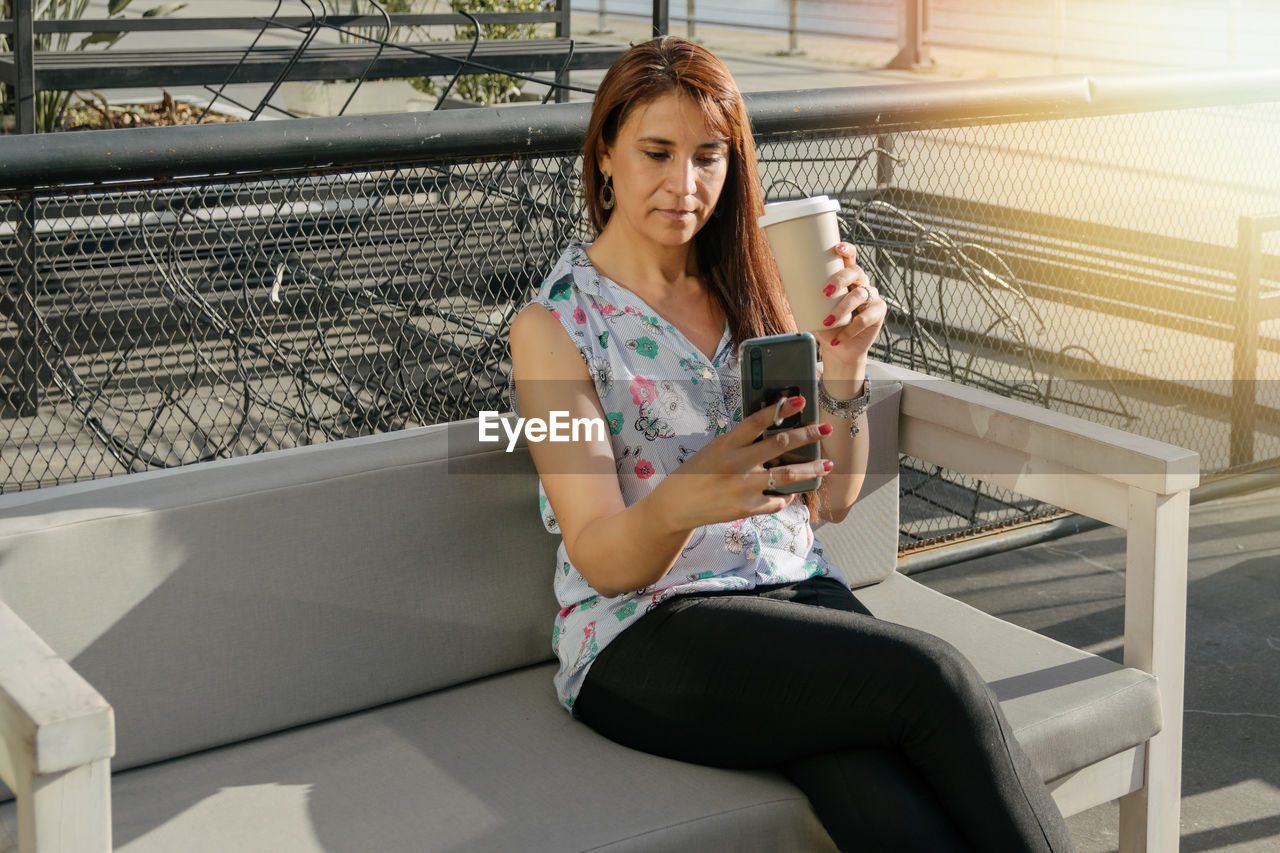 FULL LENGTH OF YOUNG WOMAN USING MOBILE PHONE WHILE SITTING ON CAMERA