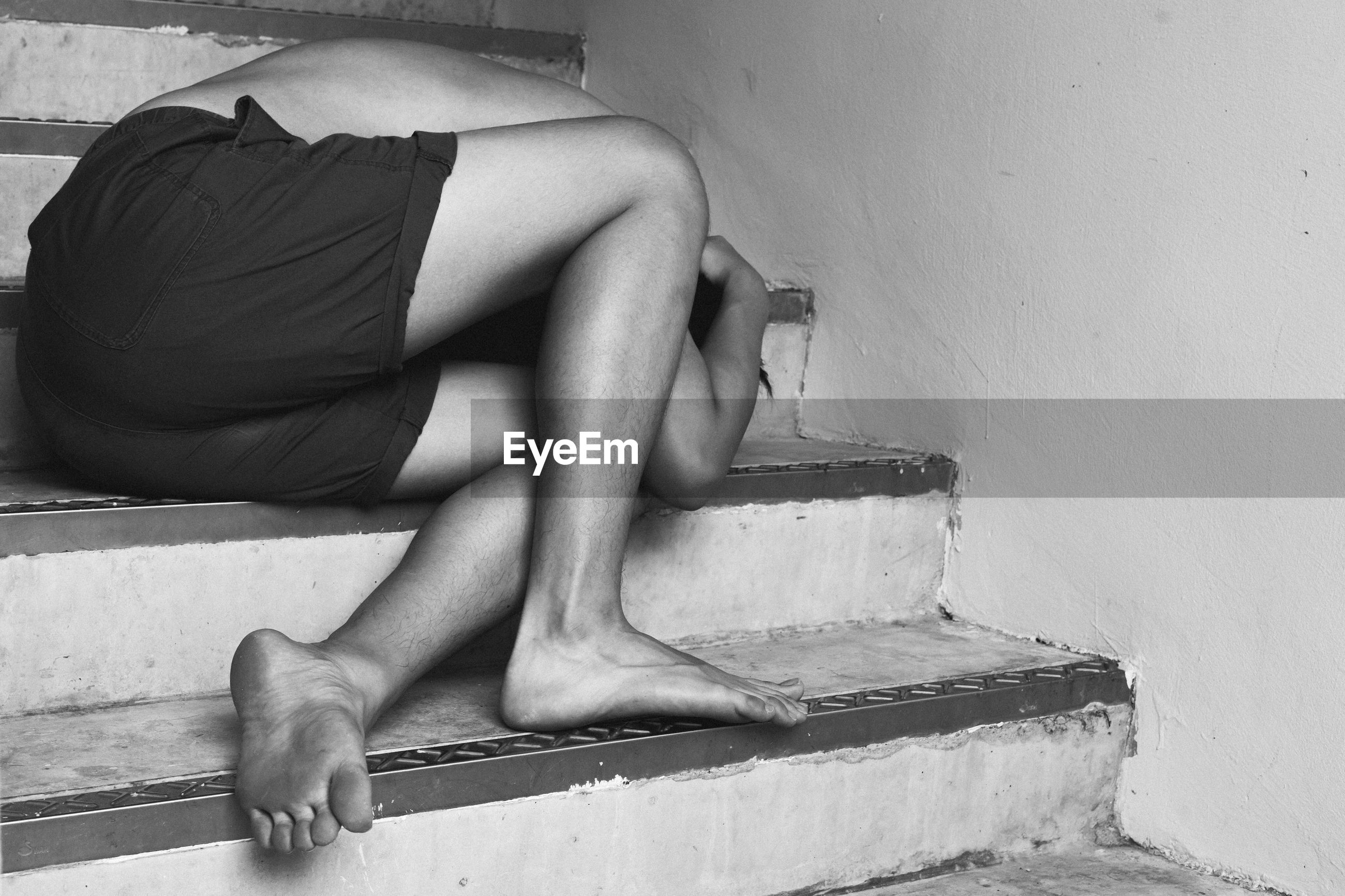 LOW SECTION OF WOMAN SITTING ON STEPS AGAINST WALL