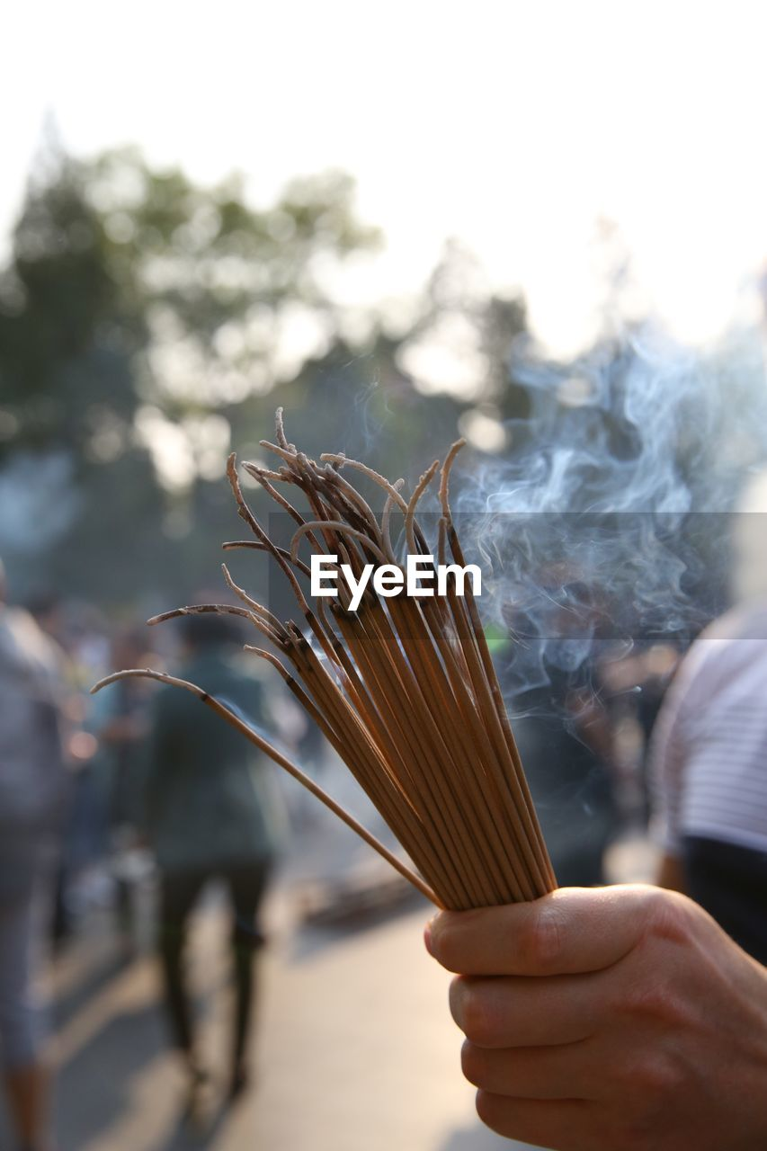 Close-up of hand holding burning incense sticks