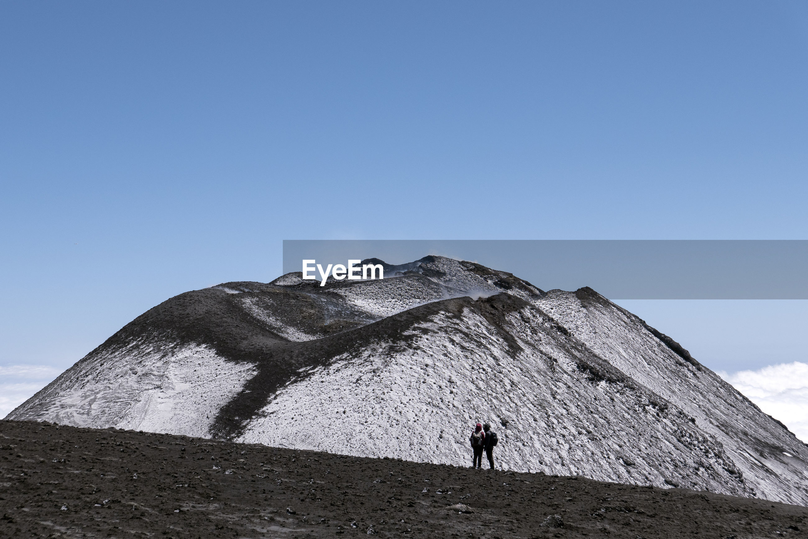 FULL LENGTH OF MAN STANDING ON MOUNTAIN AGAINST CLEAR SKY