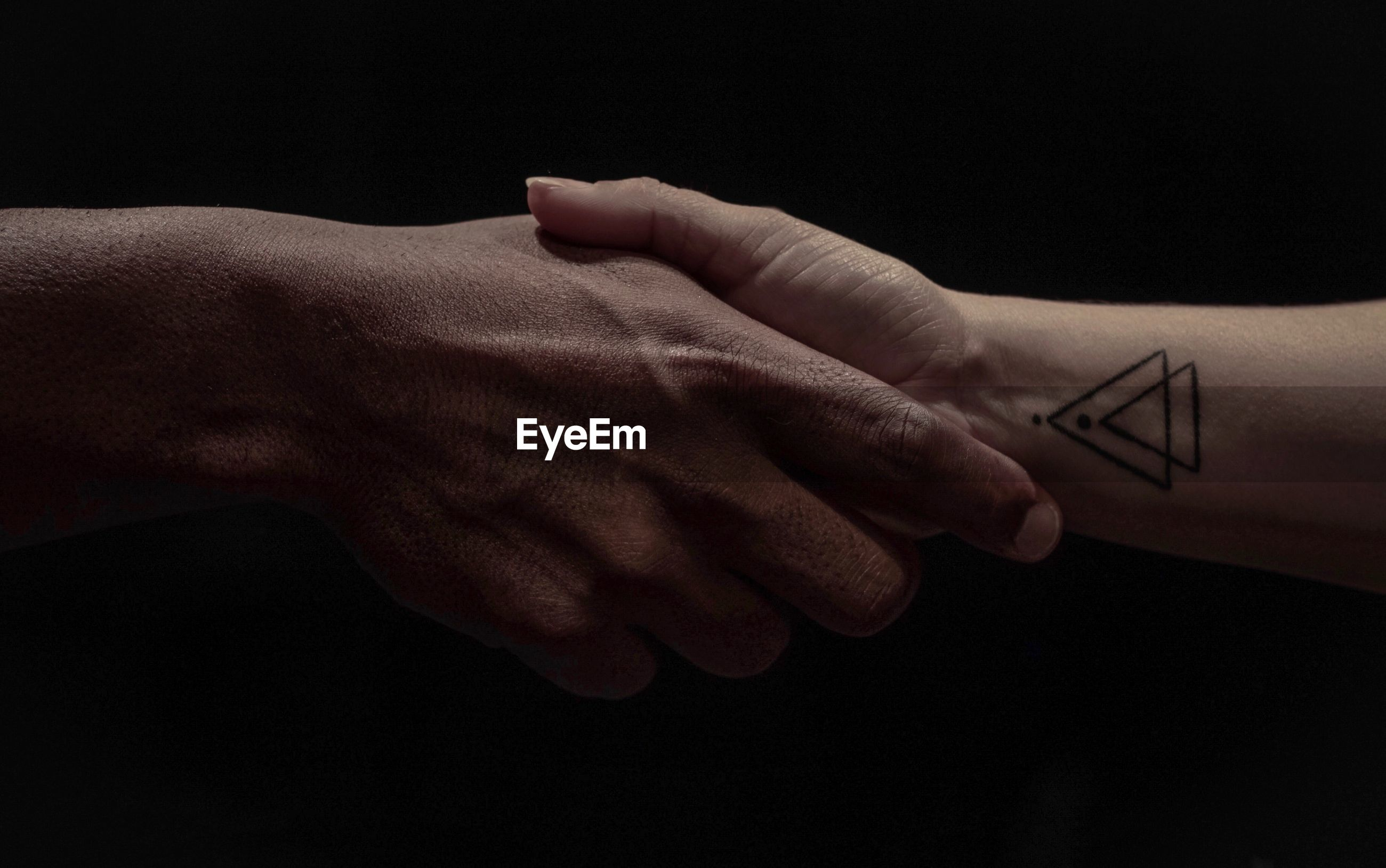 Cropped image of people shaking hands against black background