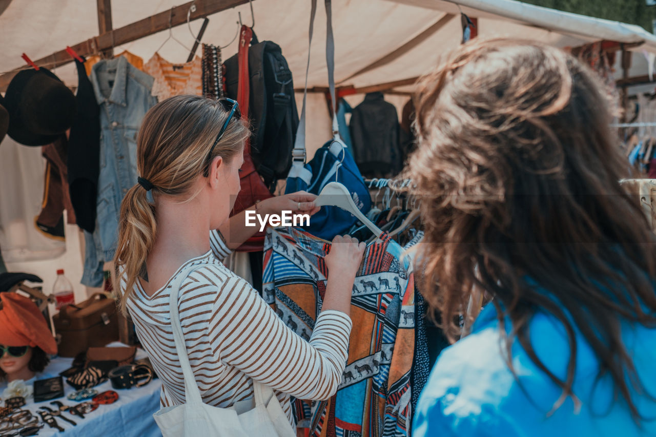 Woman with friend buying clothes at market
