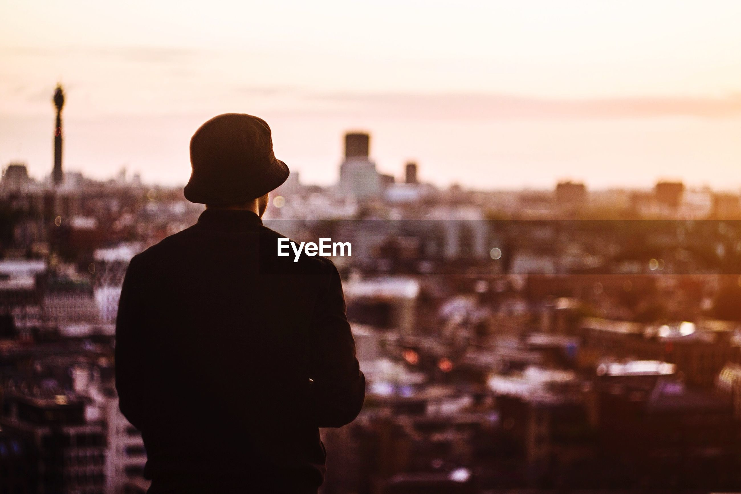 Rear view of man wearing hat looking at cityscape during sunset
