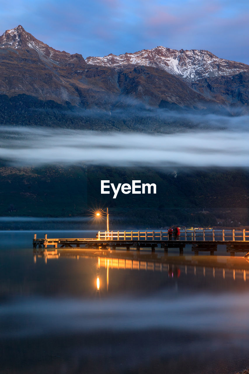 water, sky, mountain, scenics - nature, waterfront, beauty in nature, nature, cloud - sky, sea, reflection, non-urban scene, built structure, architecture, no people, night, illuminated, tranquil scene, mountain range, outdoors, snowcapped mountain