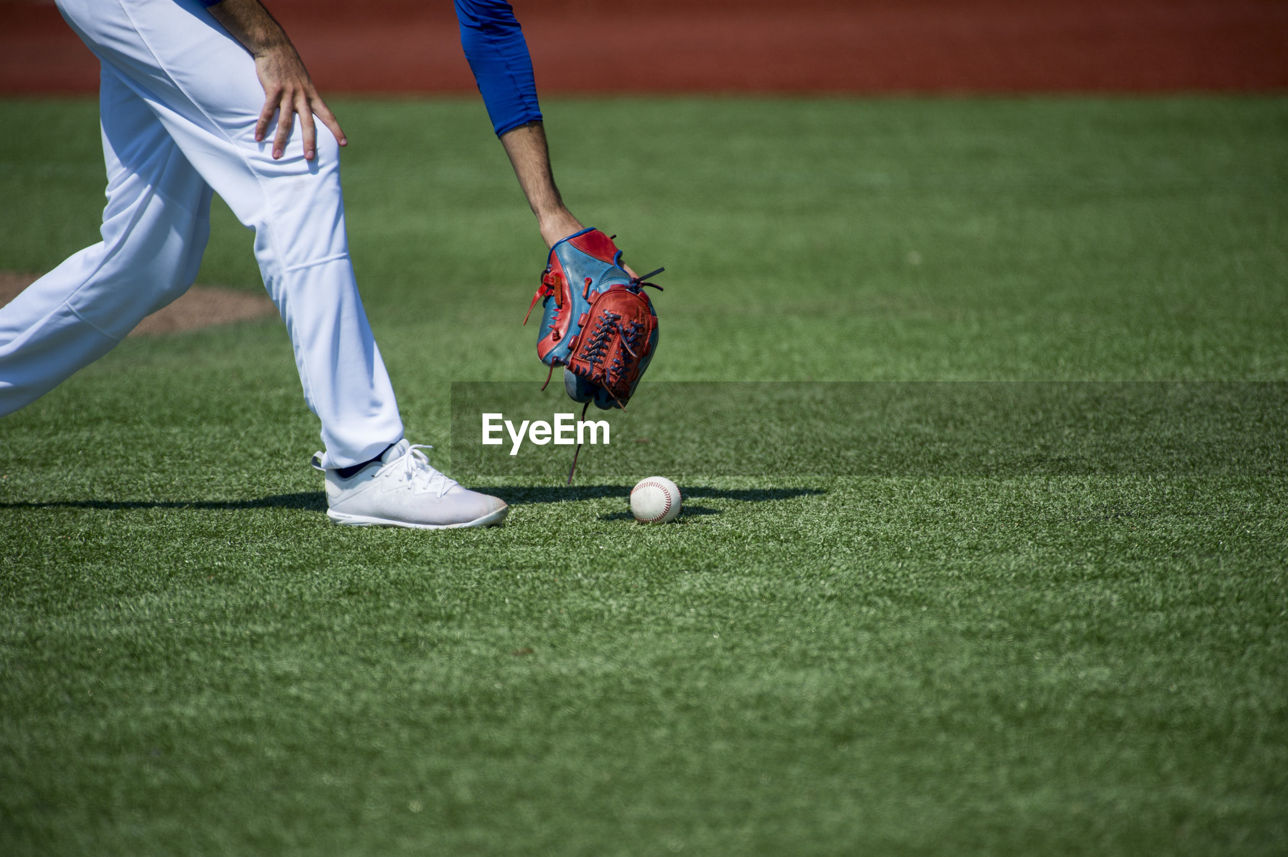 Low section of player picking baseball on grass