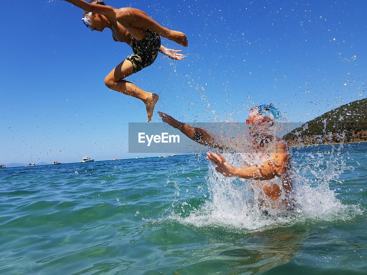 water, motion, splashing, lifestyles, real people, shirtless, men, sea, leisure activity, sky, fun, enjoyment, two people, nature, clear sky, jumping, day, people, mid-air, outdoors, positive emotion, human arm