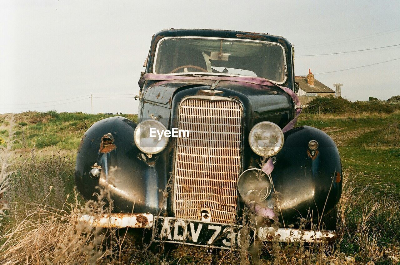 abandoned, headlight, mode of transport, obsolete, transportation, retro styled, old-fashioned, field, land vehicle, rusty, damaged, car, deterioration, bad condition, run-down, day, front view, no people, vintage, antique, outdoors, clear sky, landscape, sky, grass, close-up, nature