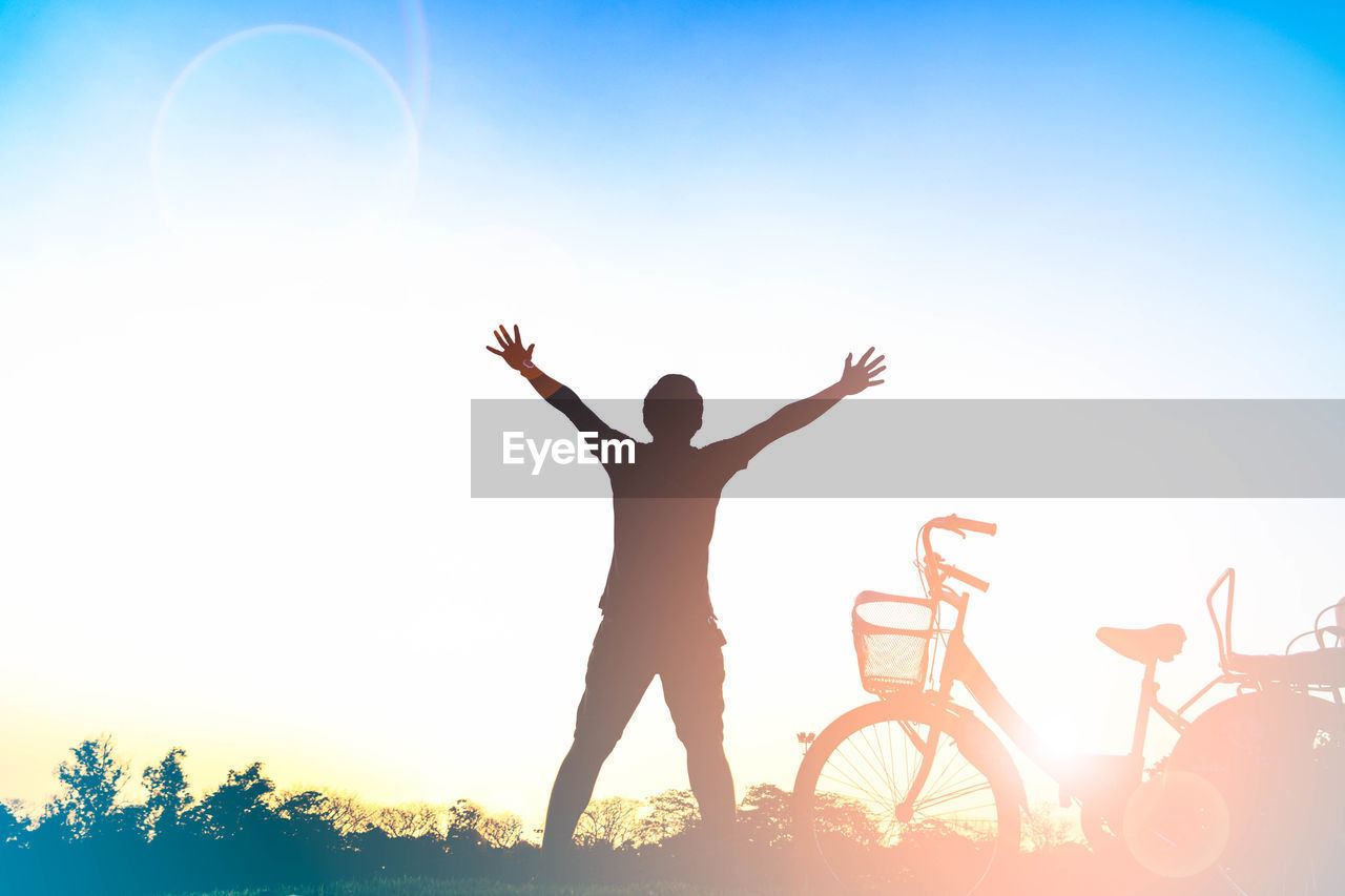 real people, bicycle, silhouette, sky, sunset, clear sky, outdoors, leisure activity, nature, transportation, sunlight, lifestyles, men, one person, beauty in nature, standing, day, people