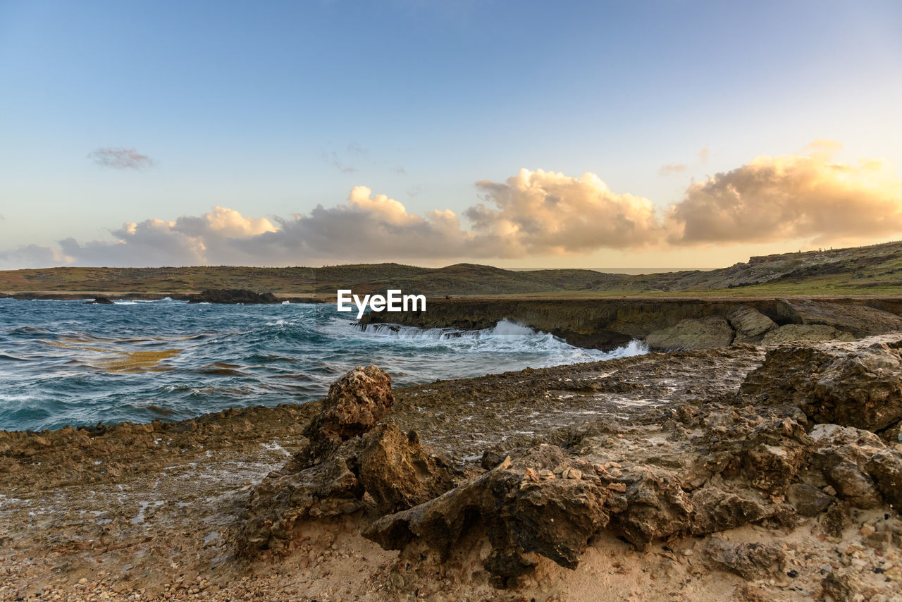 sky, scenics - nature, water, beauty in nature, land, tranquility, tranquil scene, beach, sea, cloud - sky, rock, nature, non-urban scene, no people, rock - object, solid, idyllic, day, outdoors, driftwood