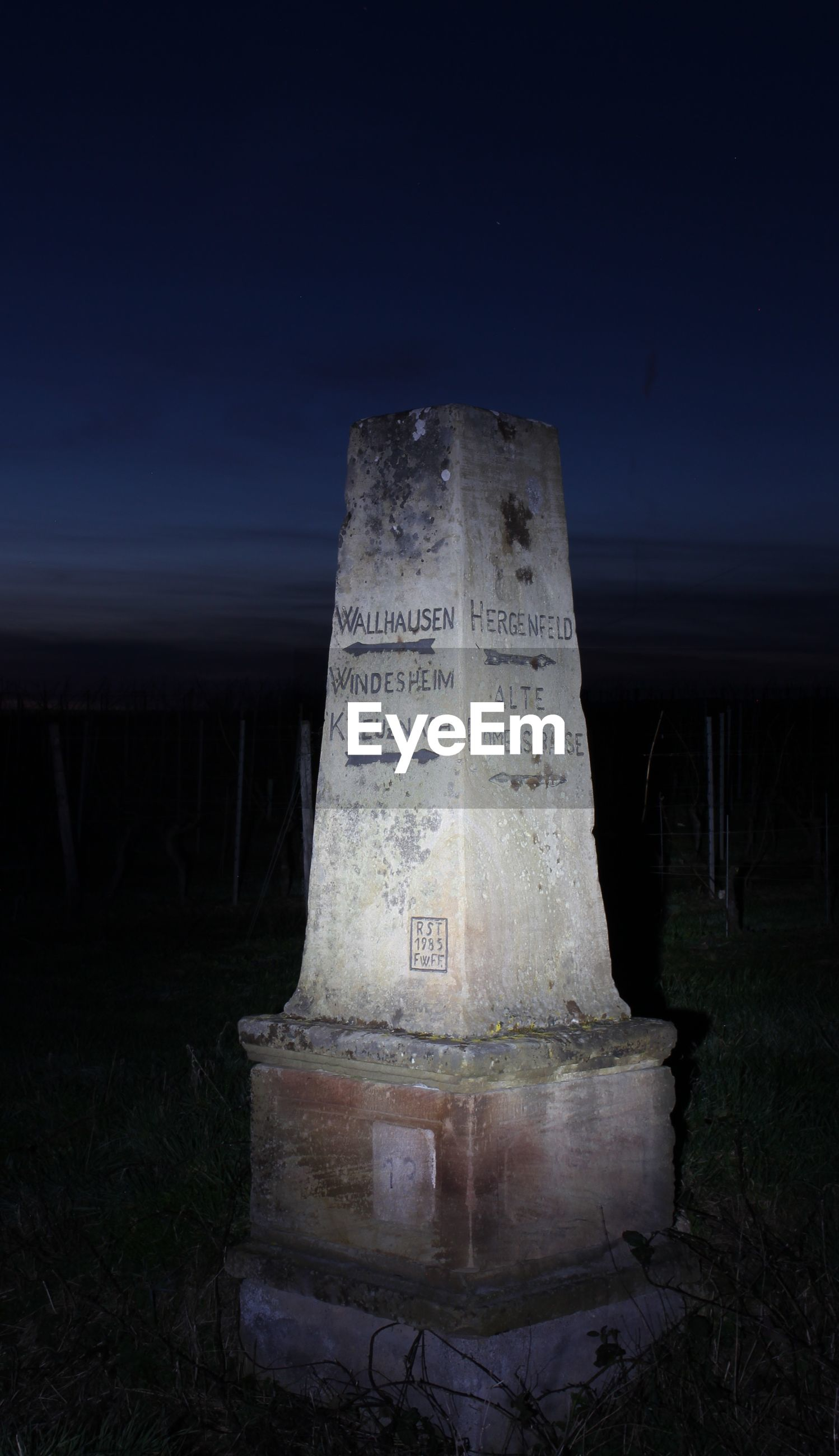 INFORMATION SIGN ON FIELD AGAINST CLEAR SKY AT NIGHT