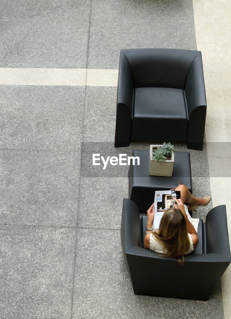 high angle view, sitting, technology, one person, communication, women, young adult, relaxation, wireless technology, day, casual clothing, young women, real people, lying down, indoors, convenience, university student, full length, using laptop, working, one young woman only, blond hair, one woman only, adult, people, adults only