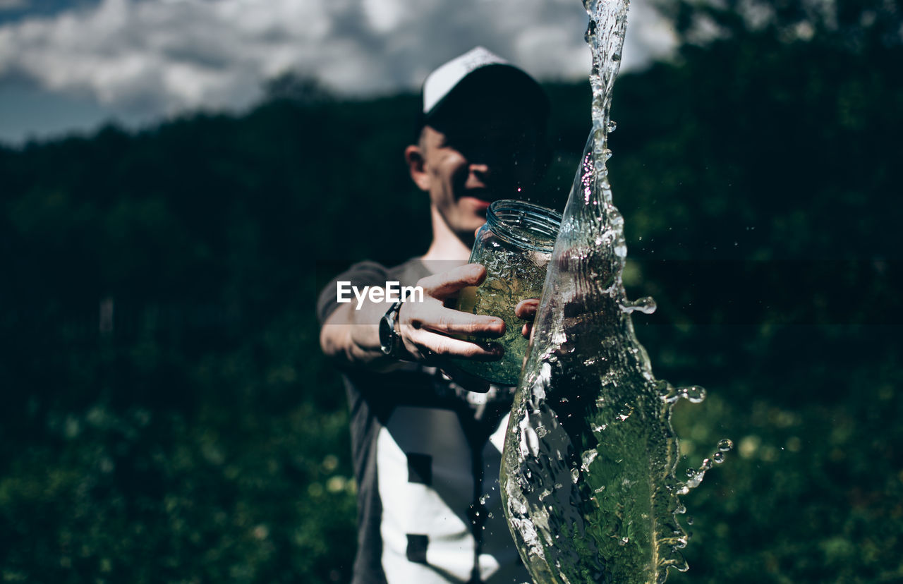 Smiling Man Throwing Water In Forest