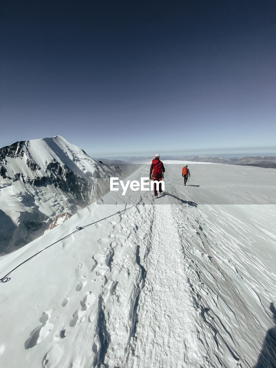 REAR VIEW OF PEOPLE ON SNOW COVERED MOUNTAIN