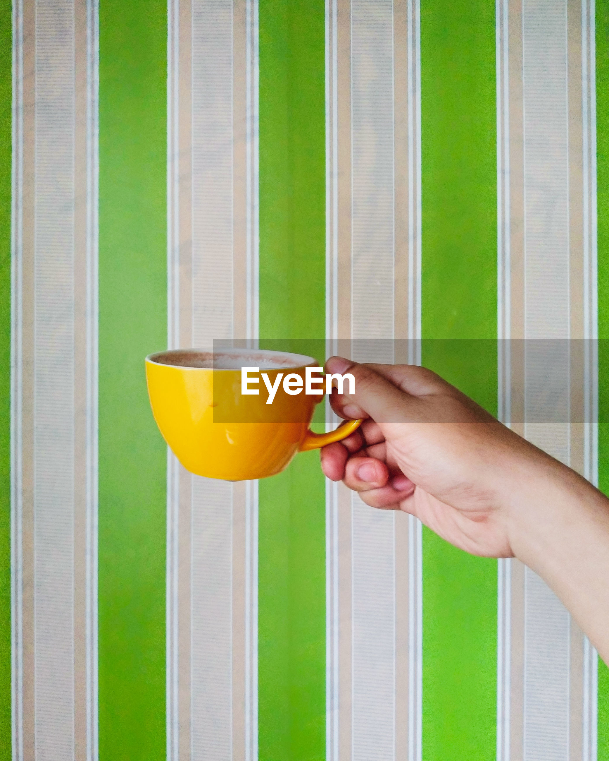 Cropped image of hand holding coffee cup on window
