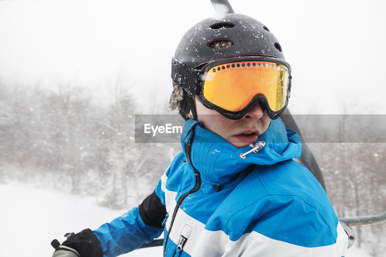 winter, snow, cold temperature, one person, clothing, leisure activity, warm clothing, helmet, mountain, ski goggles, real people, sport, winter sport, skiing helmet, lifestyles, skiing, nature, field, focus on foreground, ski-wear, outdoors, crash helmet