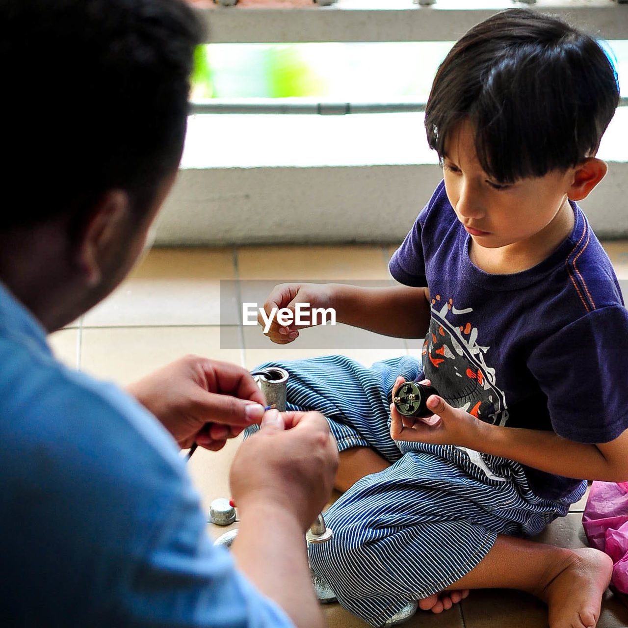 Father Teaching Scientific Experiment To Son At Home