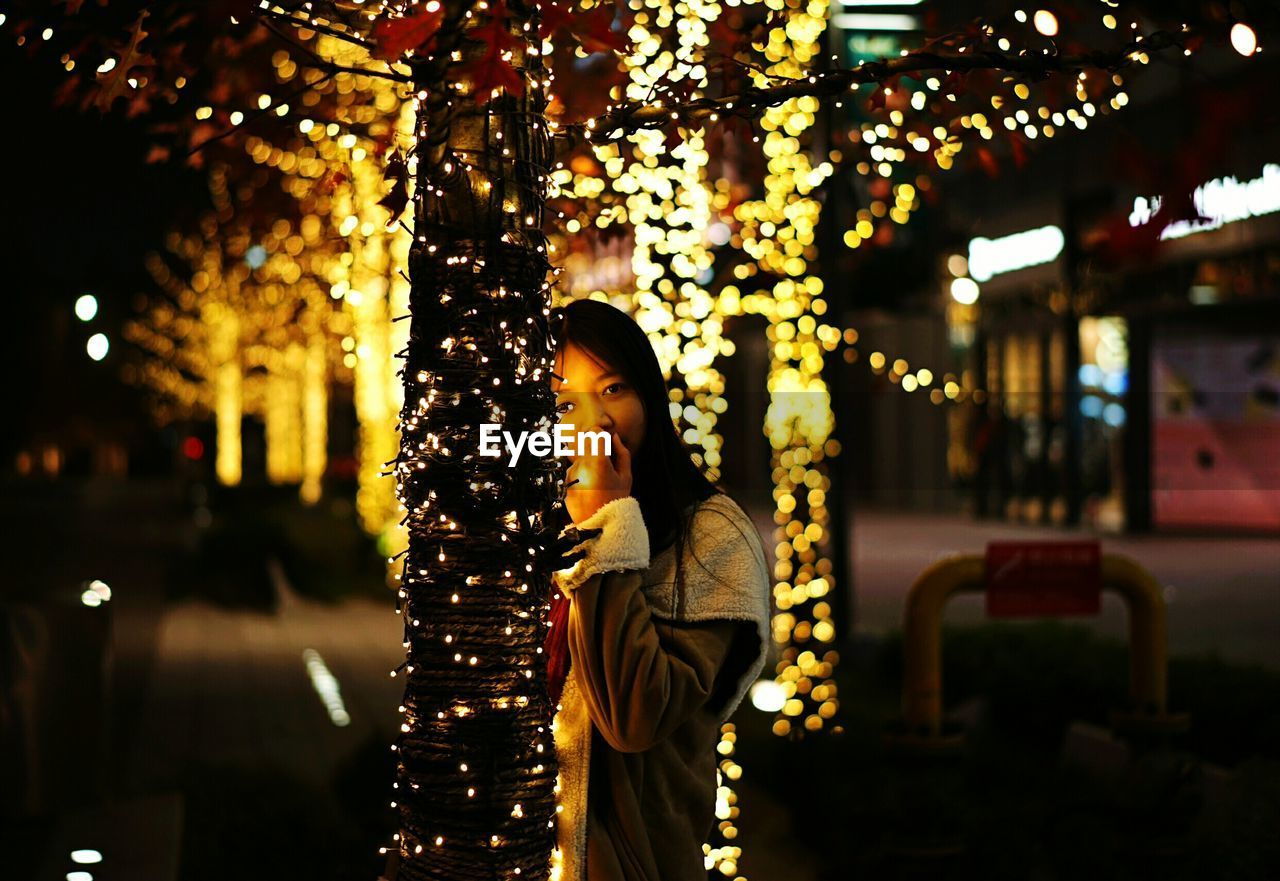 Young Woman With Christmas Tree In City At Night