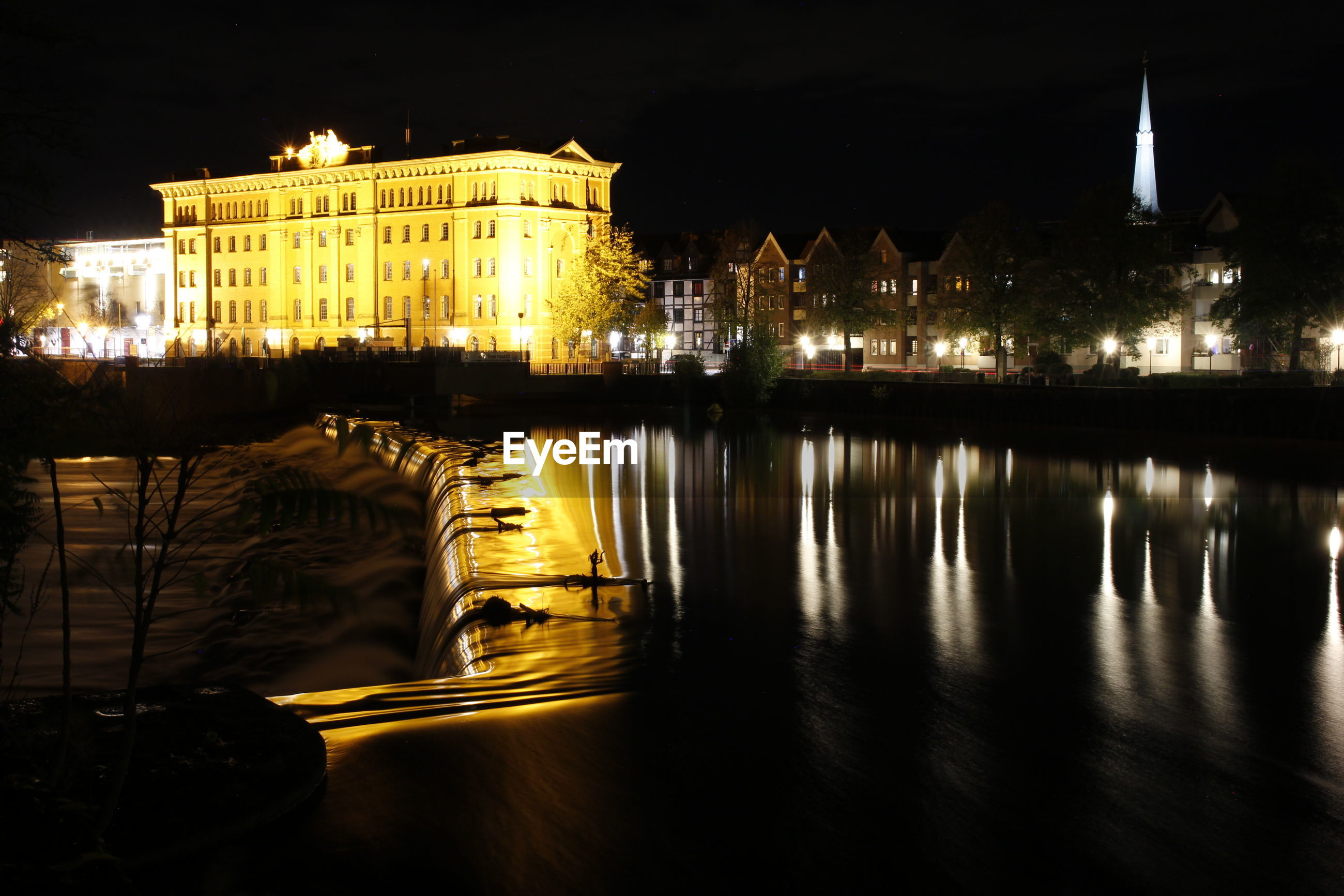 Reflection of buildings in river at night