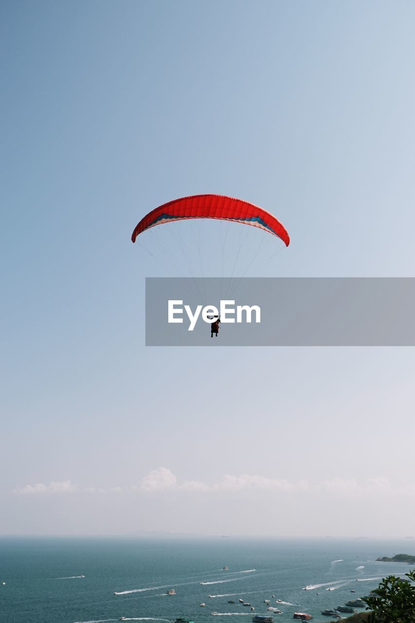 Low angle view of man paragliding over sea against clear sky