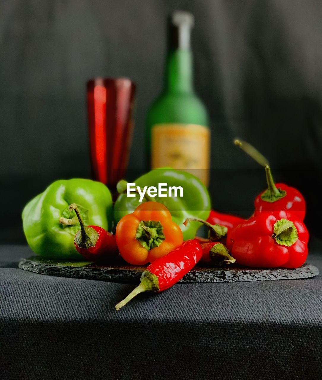 CLOSE-UP OF RED CHILI PEPPERS AND VEGETABLES ON TABLE