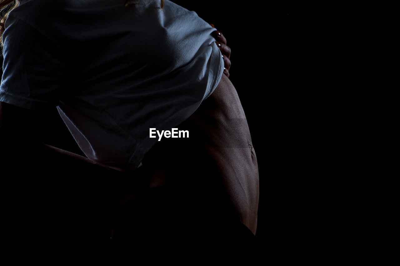 Midsection Of Woman Over Black Background