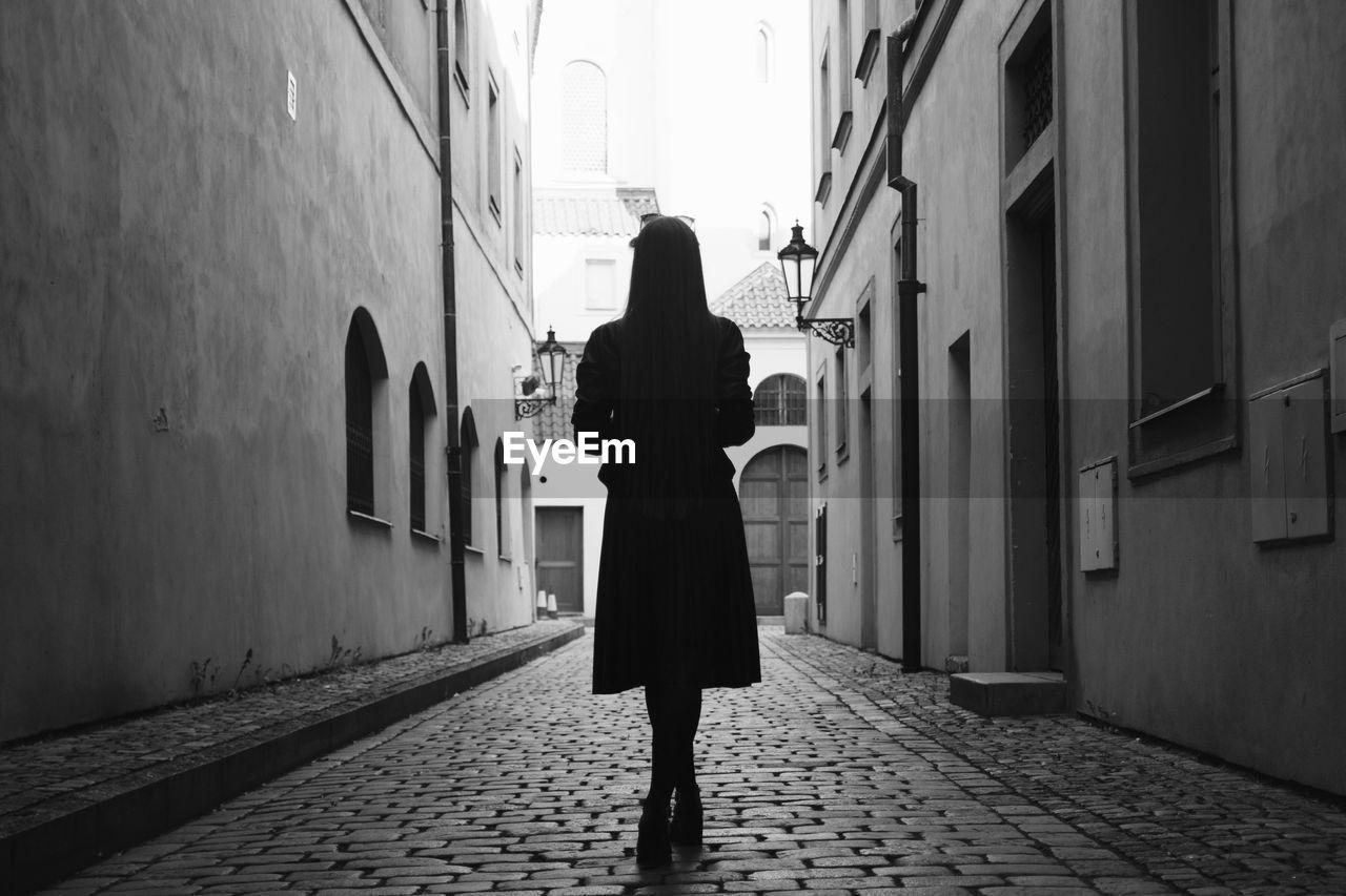 Woman Standing On Cobblestone Street