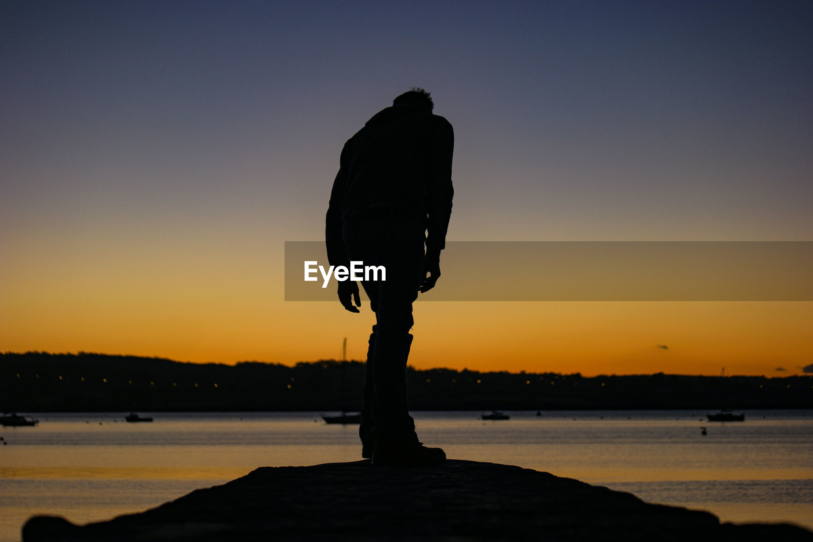 Rear view of silhouette man standing by sea against orange sky