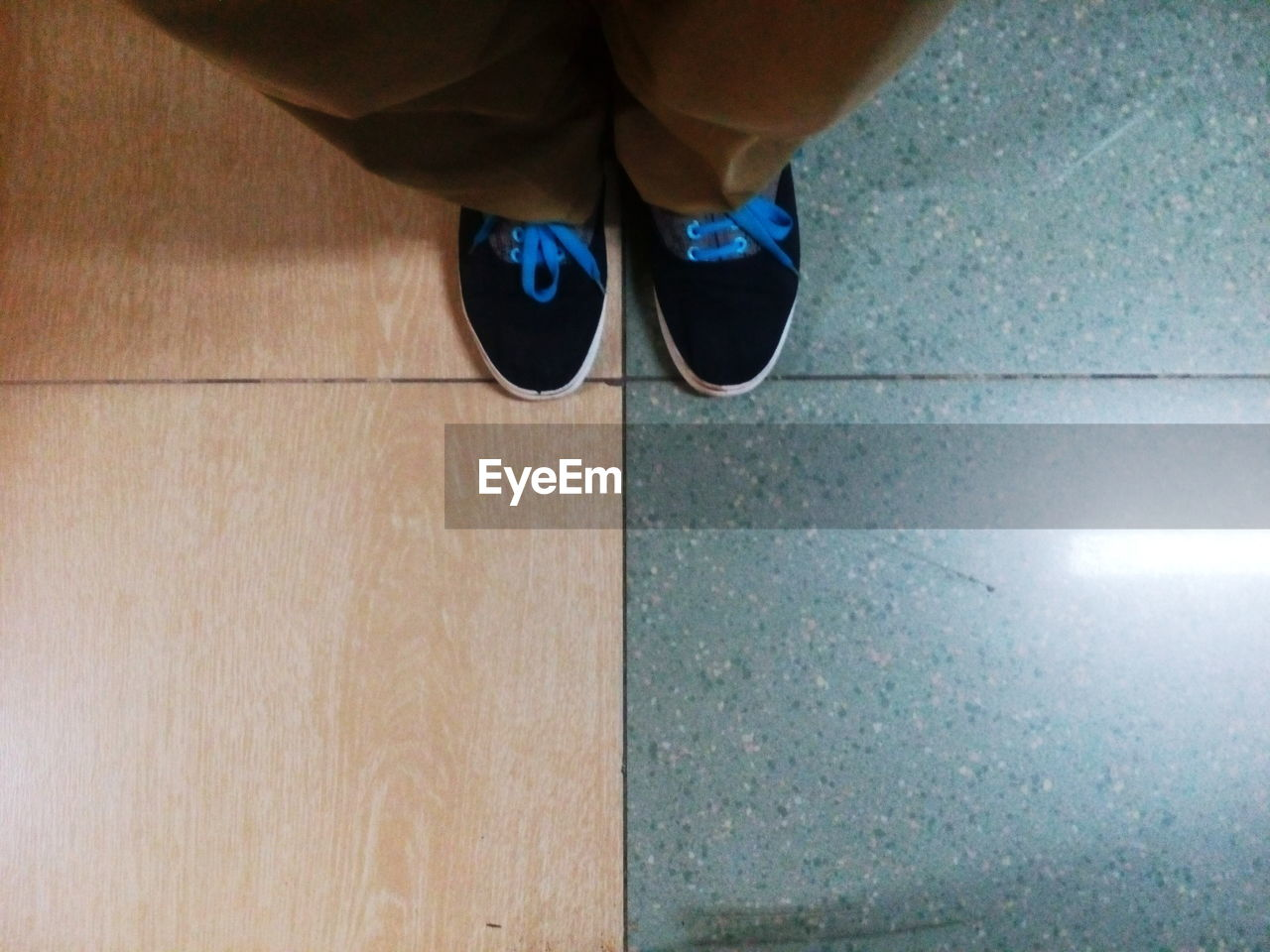 LOW SECTION OF TWO PEOPLE STANDING ON TILED FLOOR