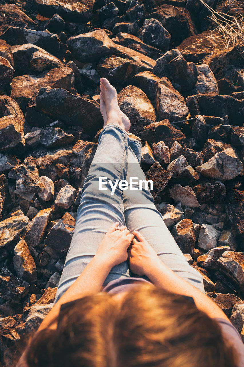 Low Section Of Woman Lying On Rock