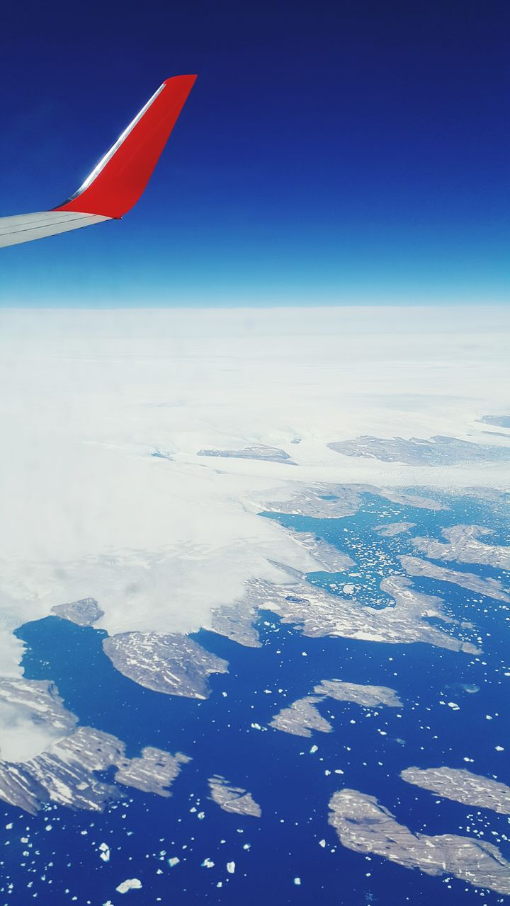 nature, beauty in nature, no people, mid-air, sea, outdoors, flying, day, blue, sky, scenics, cold temperature, winter, aerial view, airplane wing, airplane, water, snow, horizon over water, close-up