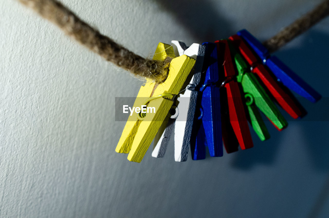 CLOSE-UP OF MULTI COLORED CLOTHESPINS HANGING ON WALL
