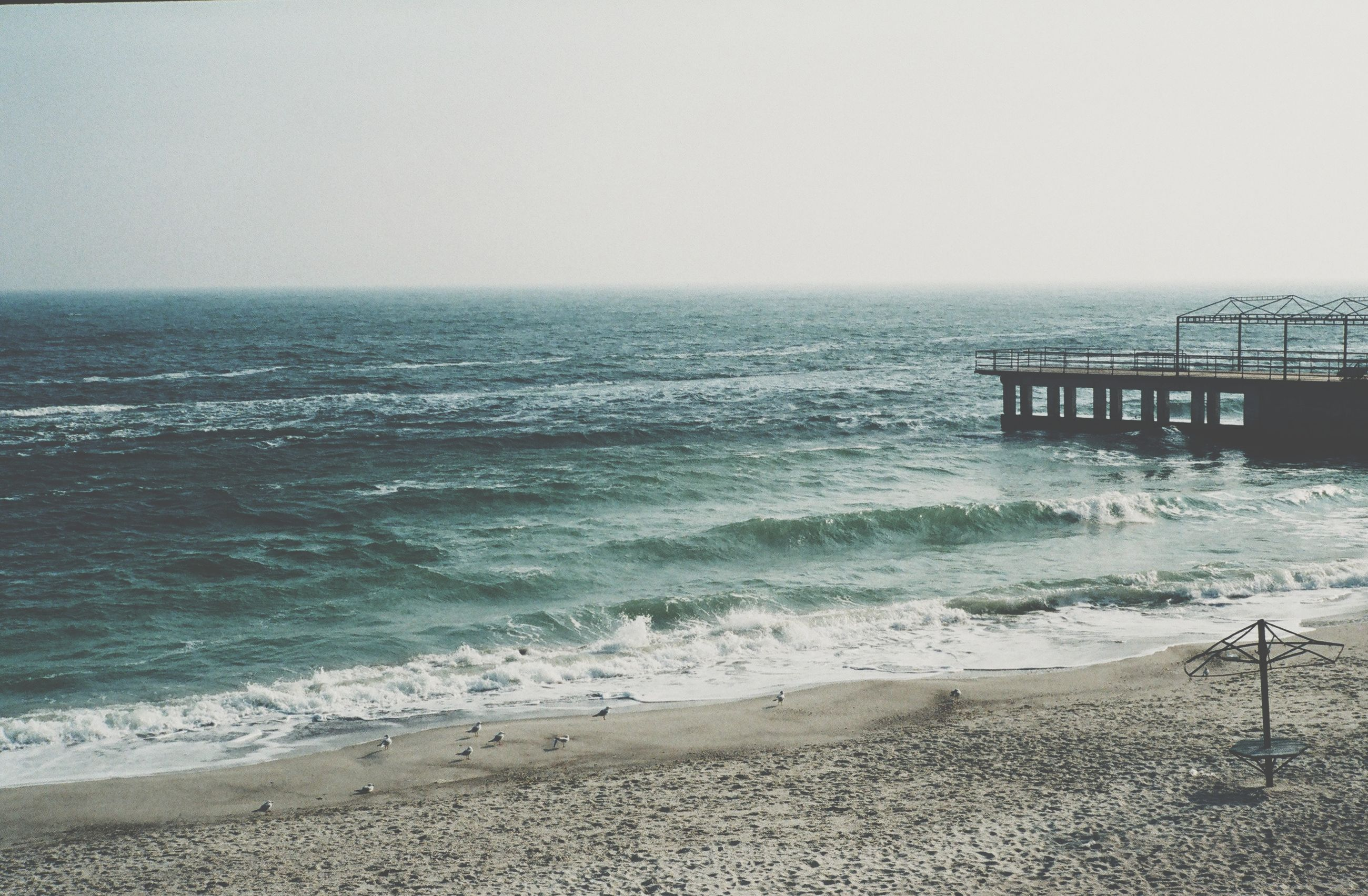 sea, horizon over water, beach, water, shore, wave, clear sky, scenics, sand, tranquil scene, tranquility, beauty in nature, surf, copy space, nature, idyllic, sky, incidental people, coastline, remote
