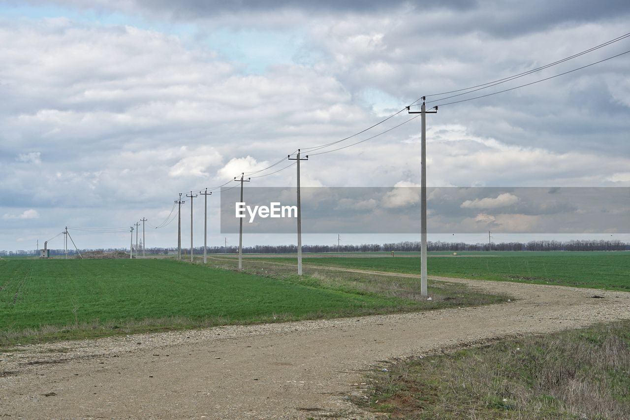 cloud - sky, cable, sky, day, connection, no people, field, power line, electricity pylon, grass, outdoors, electricity, nature, landscape, beauty in nature