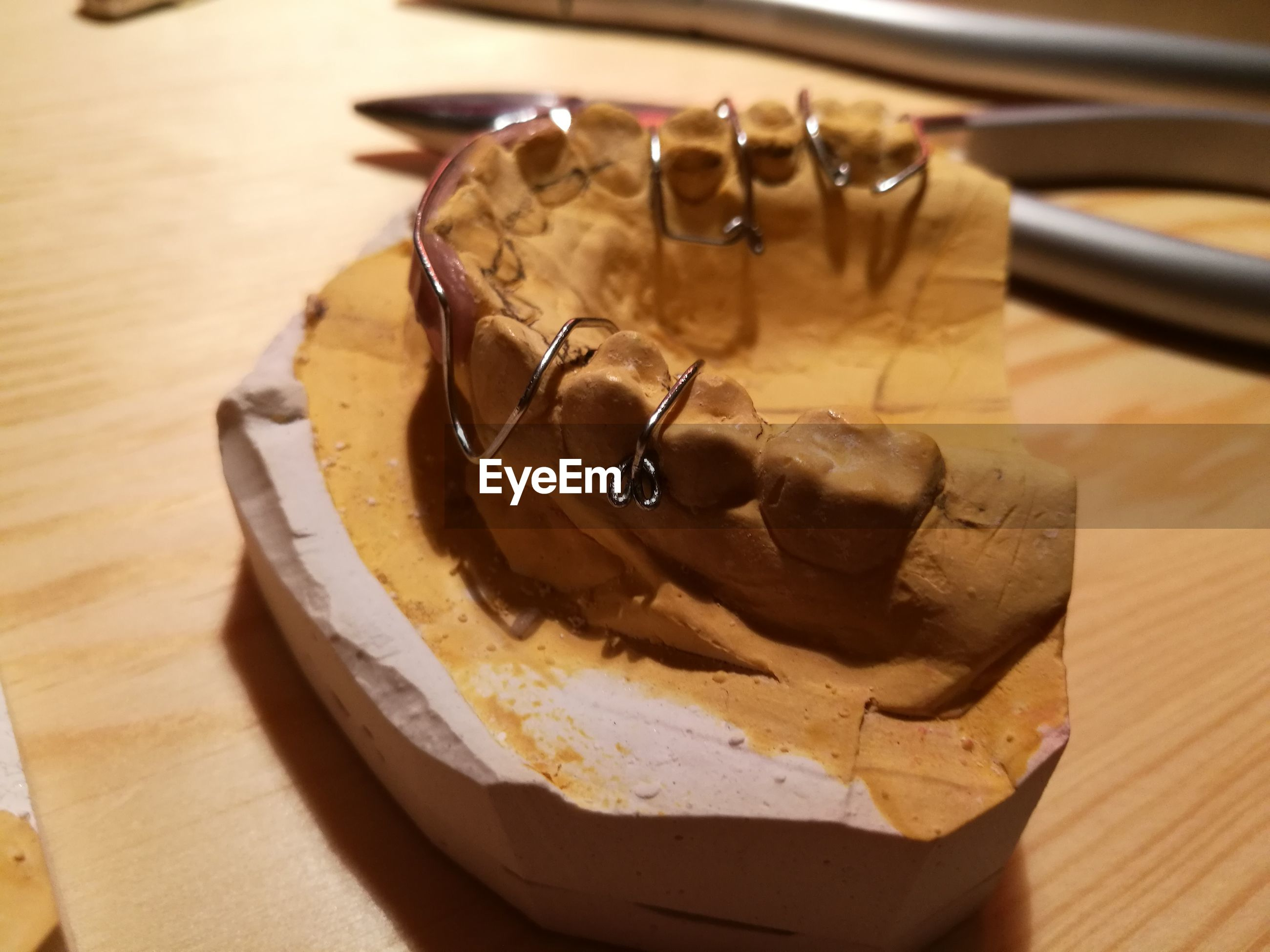 Close-up of braces on dentures over table