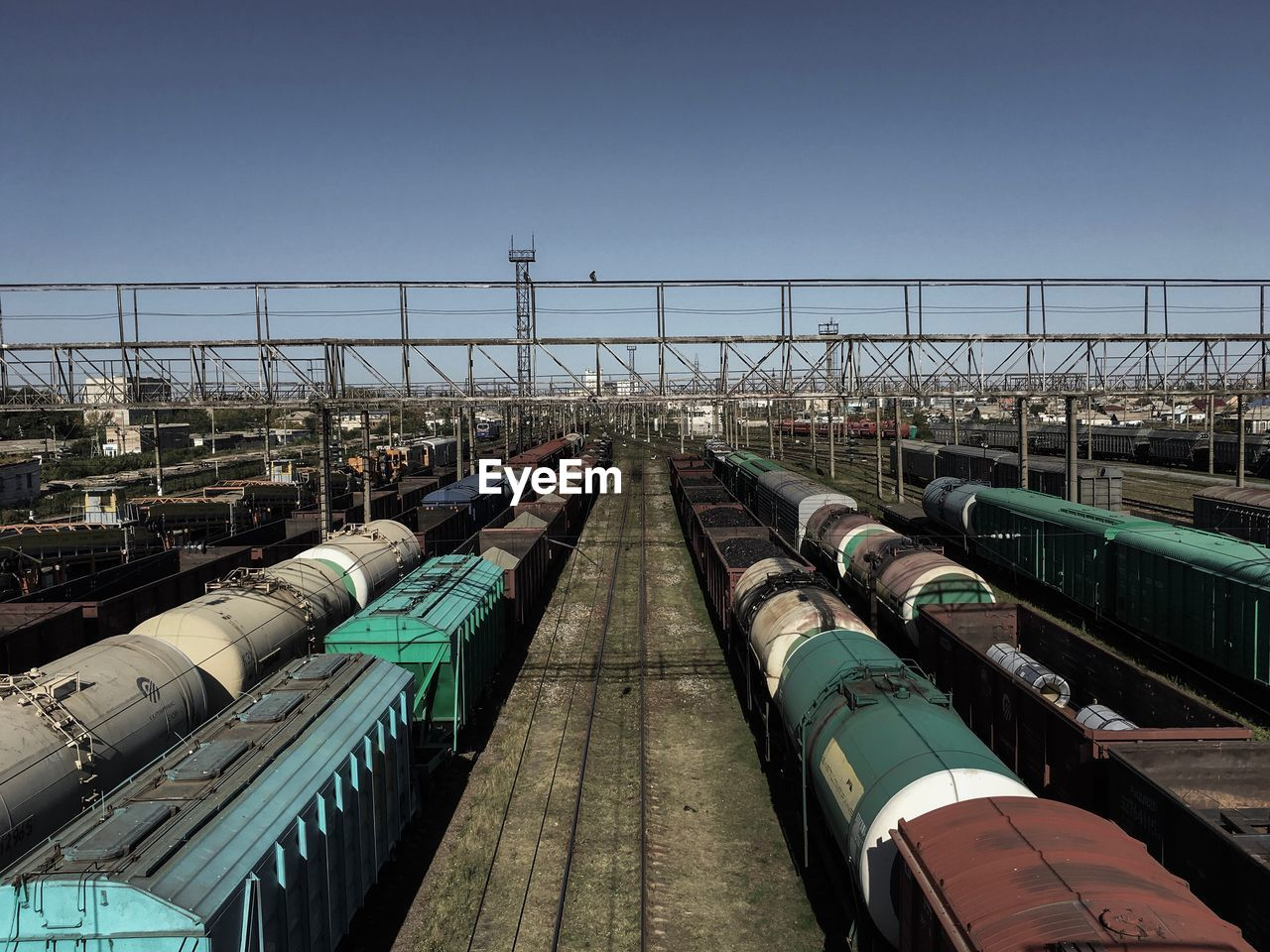 sky, clear sky, copy space, nature, day, in a row, no people, industry, transportation, side by side, built structure, architecture, fuel and power generation, outdoors, container, large group of objects, pipe - tube, blue, abundance, mode of transportation, fuel storage tank, shunting yard