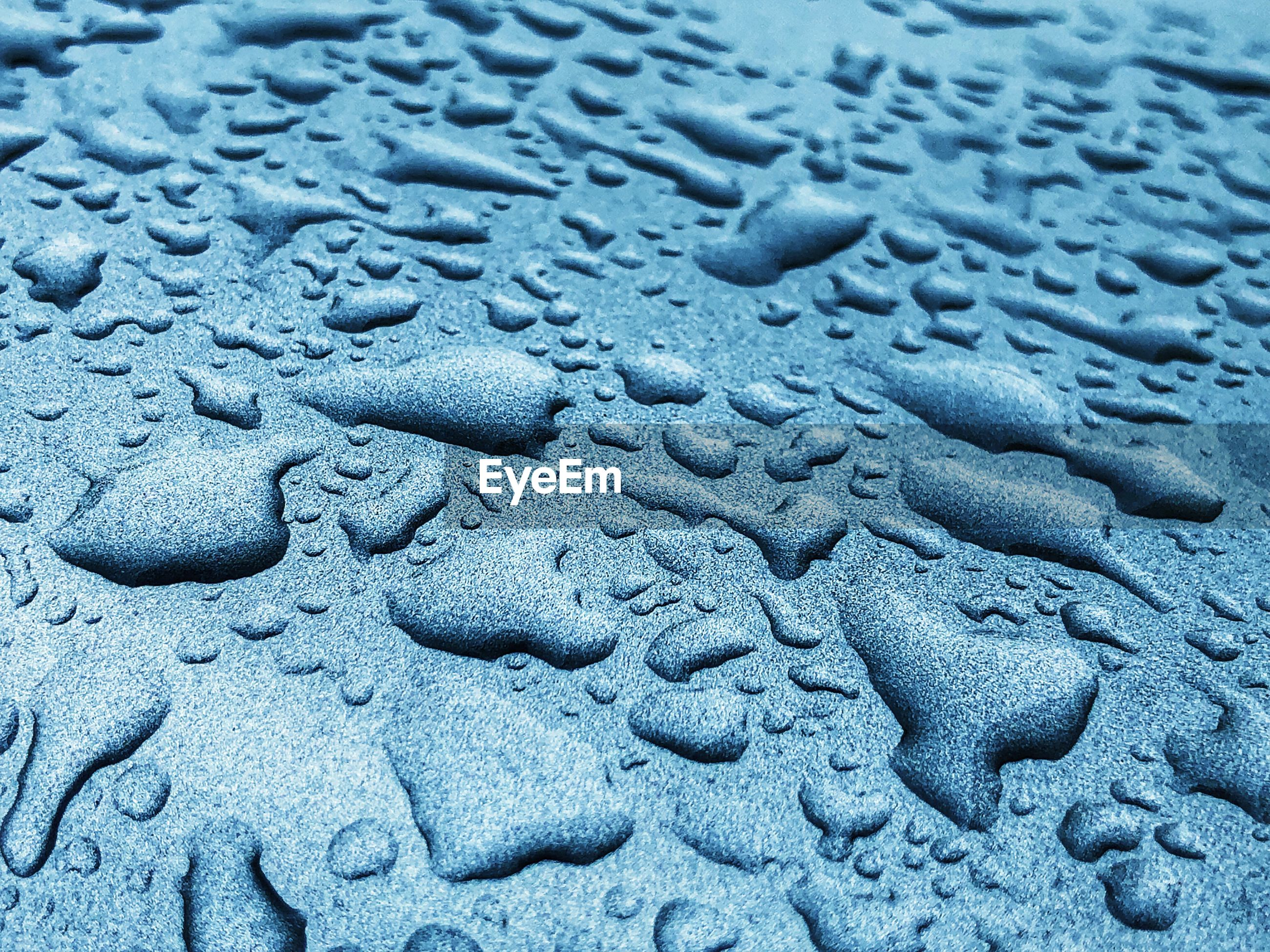 Macro shot of water drops on metal surface