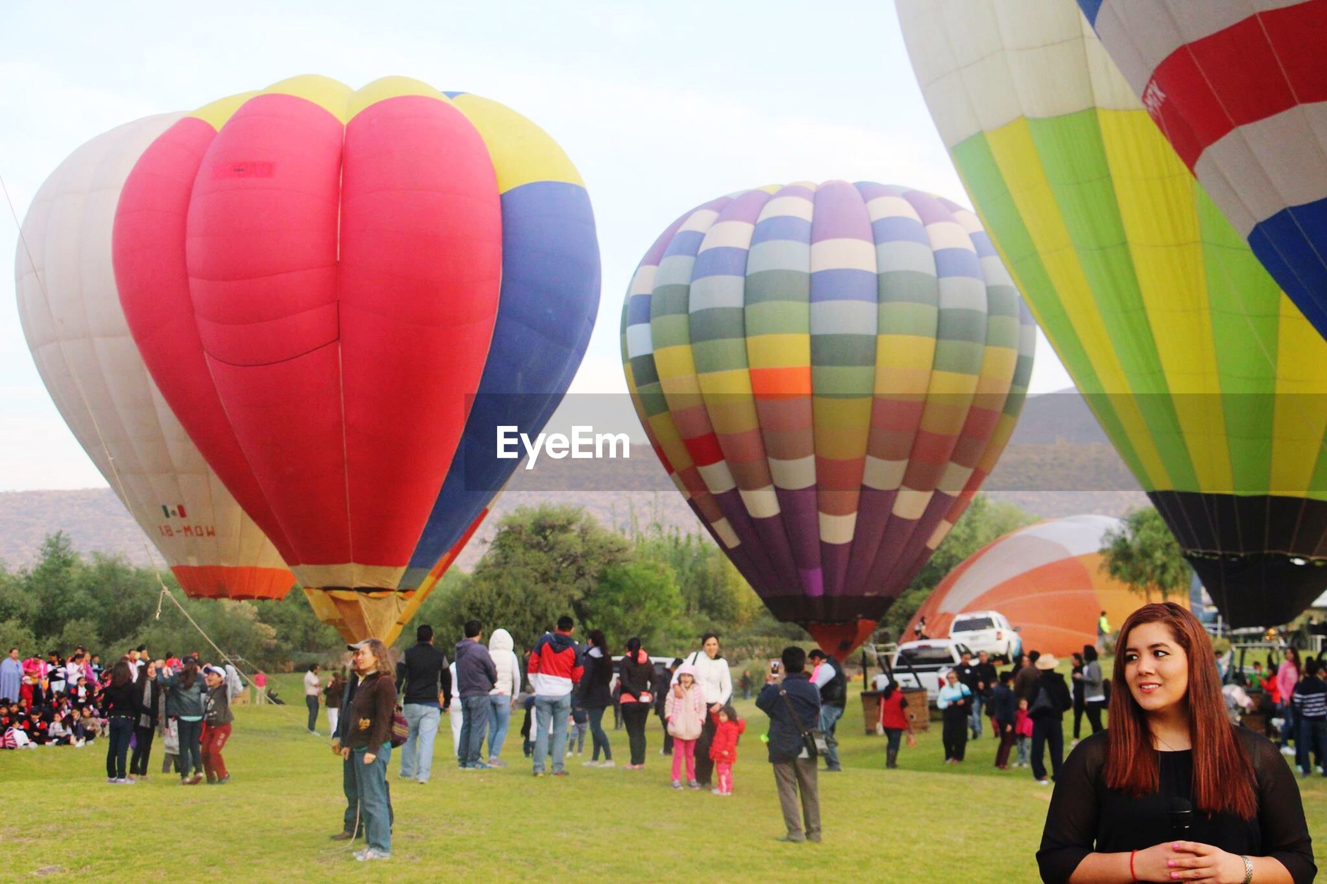 leisure activity, large group of people, lifestyles, hot air balloon, men, sport, multi colored, transportation, person, mid-air, flying, sky, travel, umbrella, parachute, adventure, tourist, tent, enjoyment