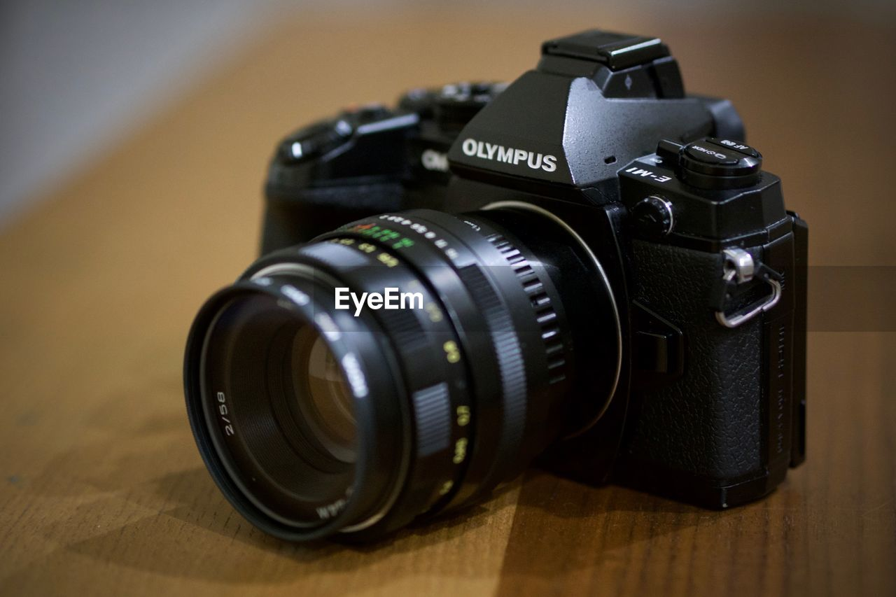 photography themes, camera - photographic equipment, photographic equipment, lens - optical instrument, camera, table, technology, indoors, black color, digital camera, still life, focus on foreground, close-up, no people, number, text, modern, retro styled, photographing, slr camera