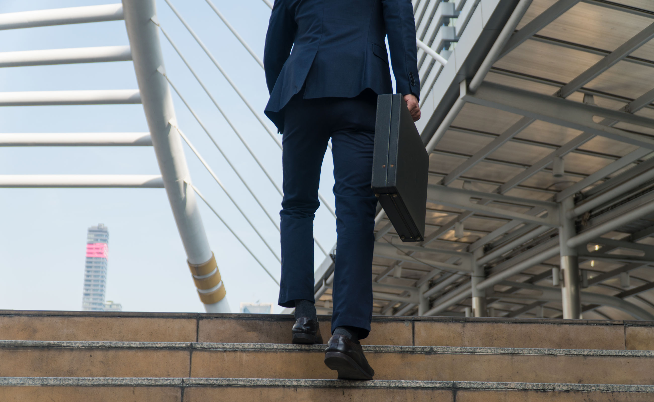 Low section of businessman walking on steps